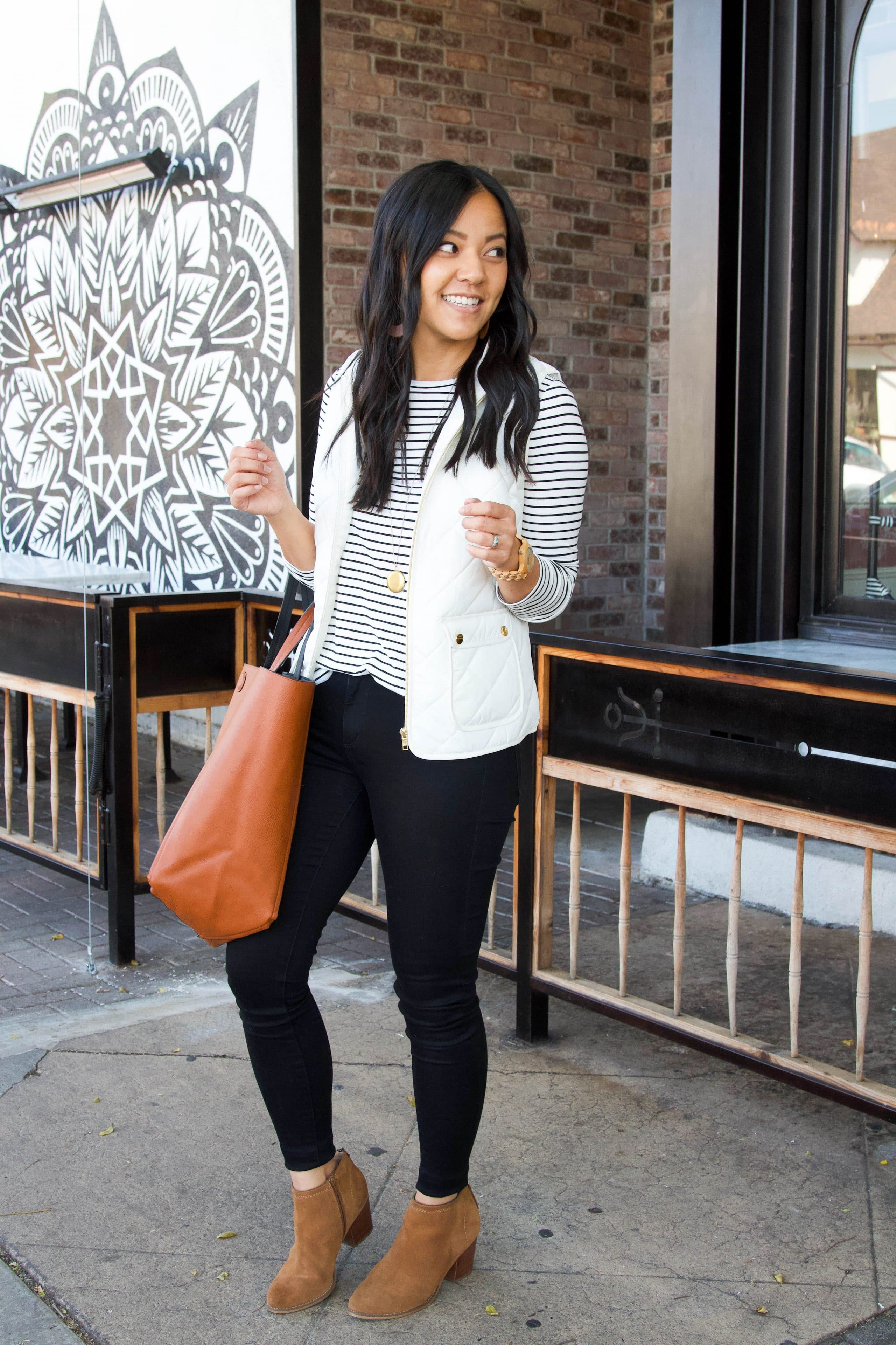white vest + black and white striped top + black pants + tan booties + cognac tote