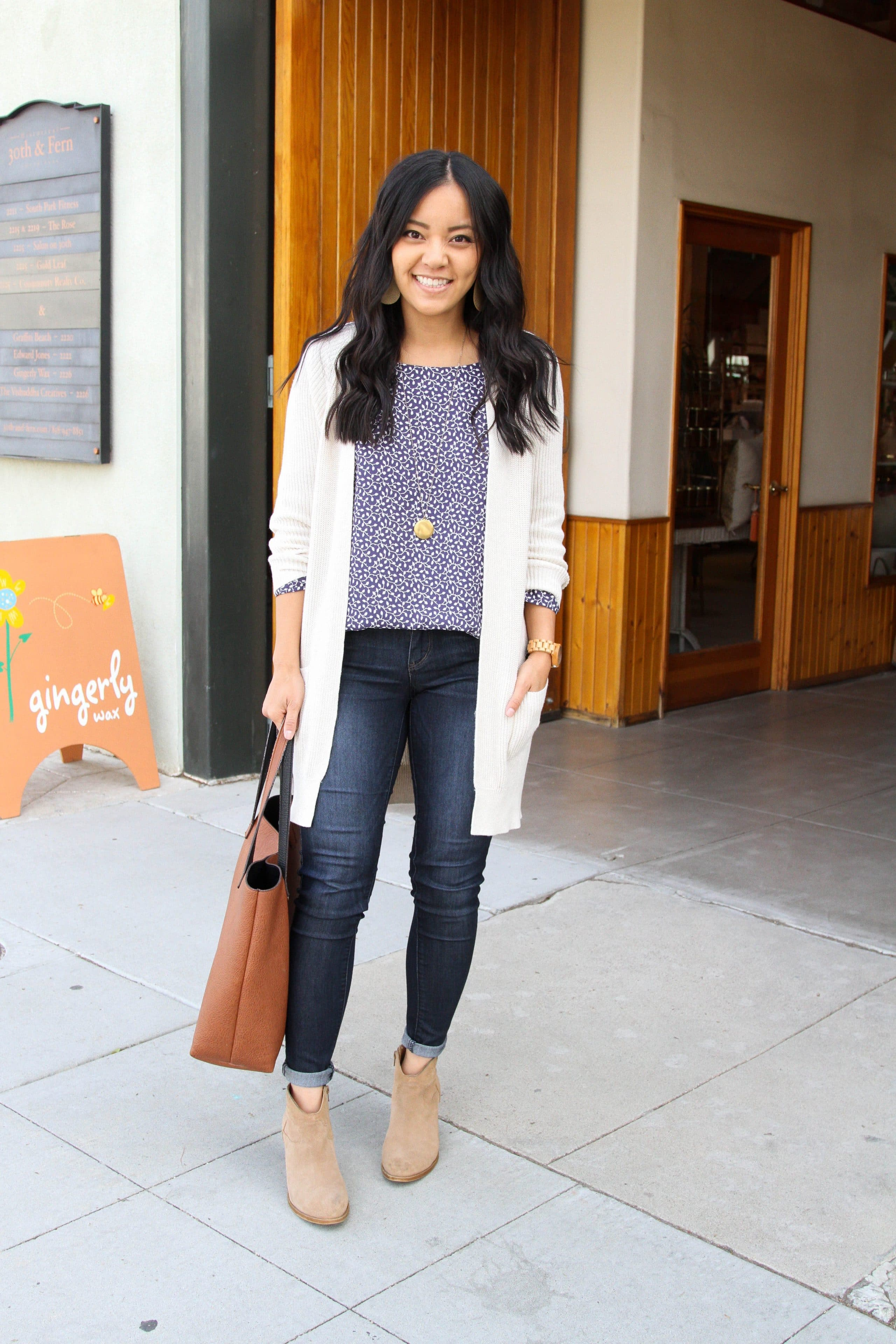 navy floral top + skinny jeans + white sweater + skinny jeans + taupe booties + cognac tote