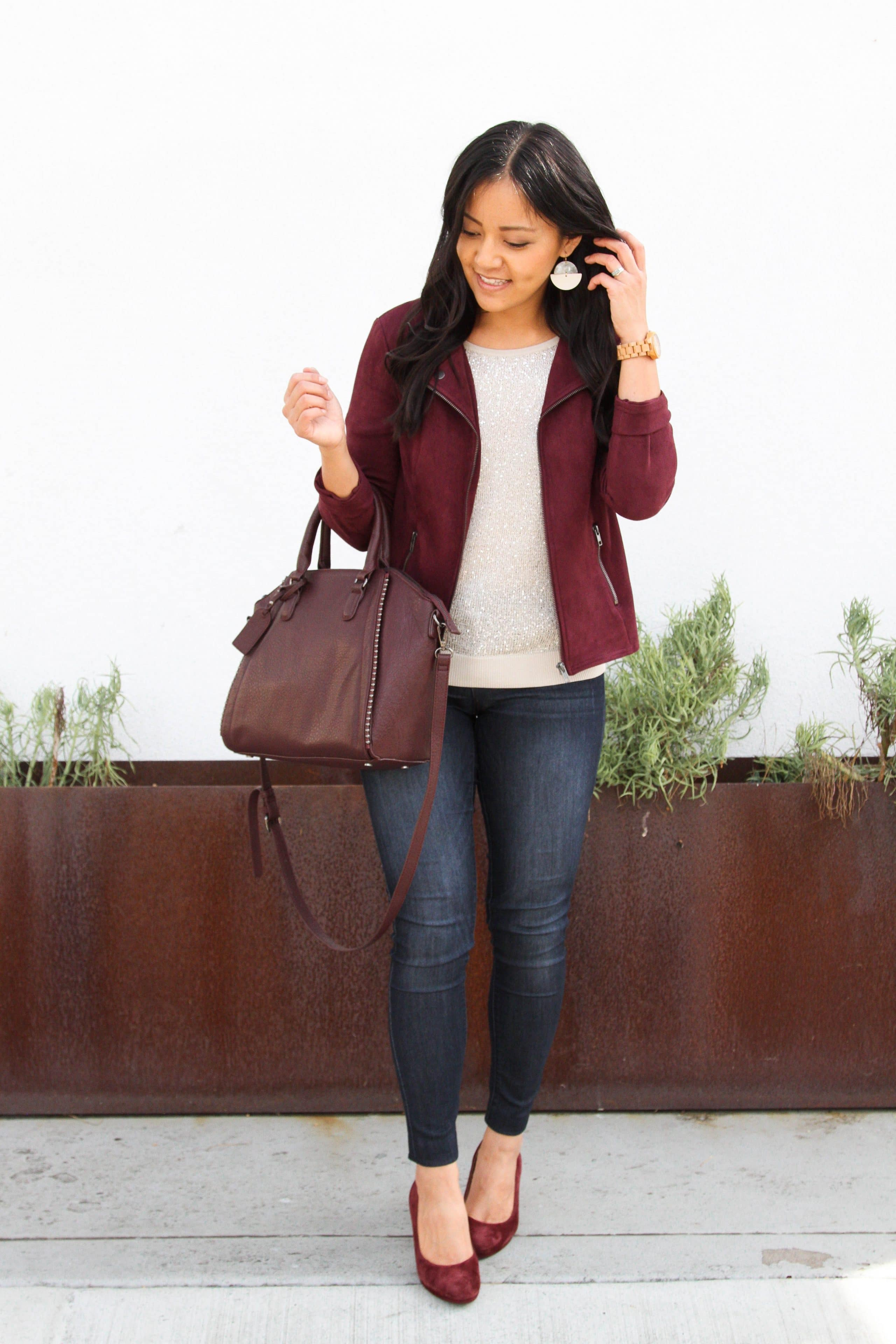 cream sequin top + maroon moto jacket + skinny jeans + maroon heels + maroon bag