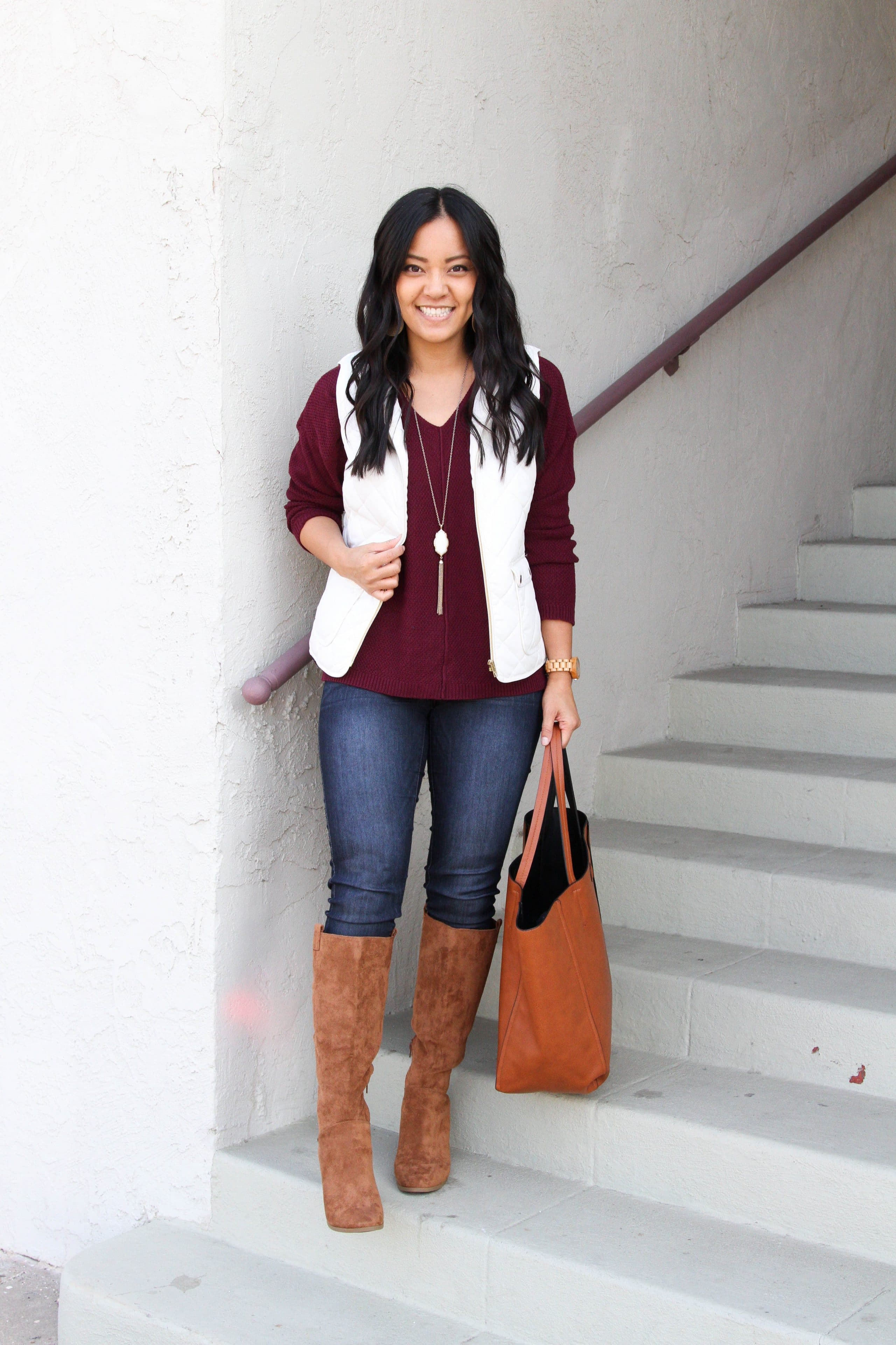 white vest + maroon sweater + skinny jeans + suede boots + cognac tote