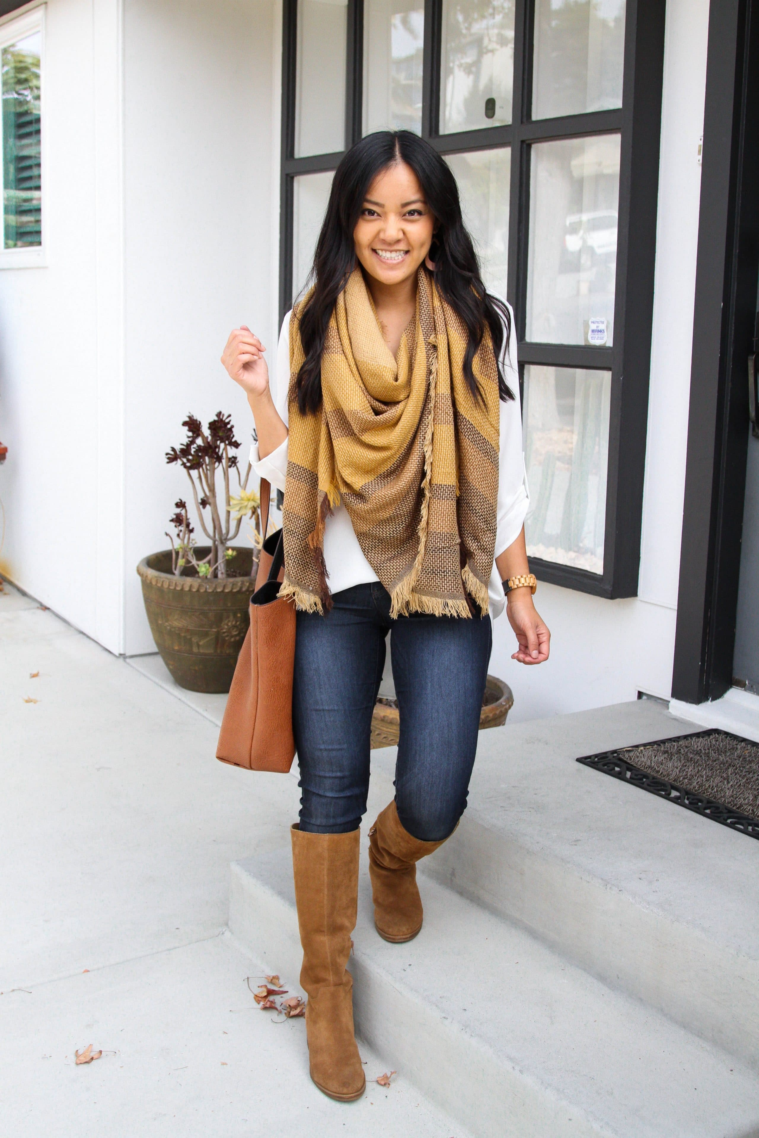 white tunic + yellow blanket scarf + skinny jeans + suede boots + cognac bag