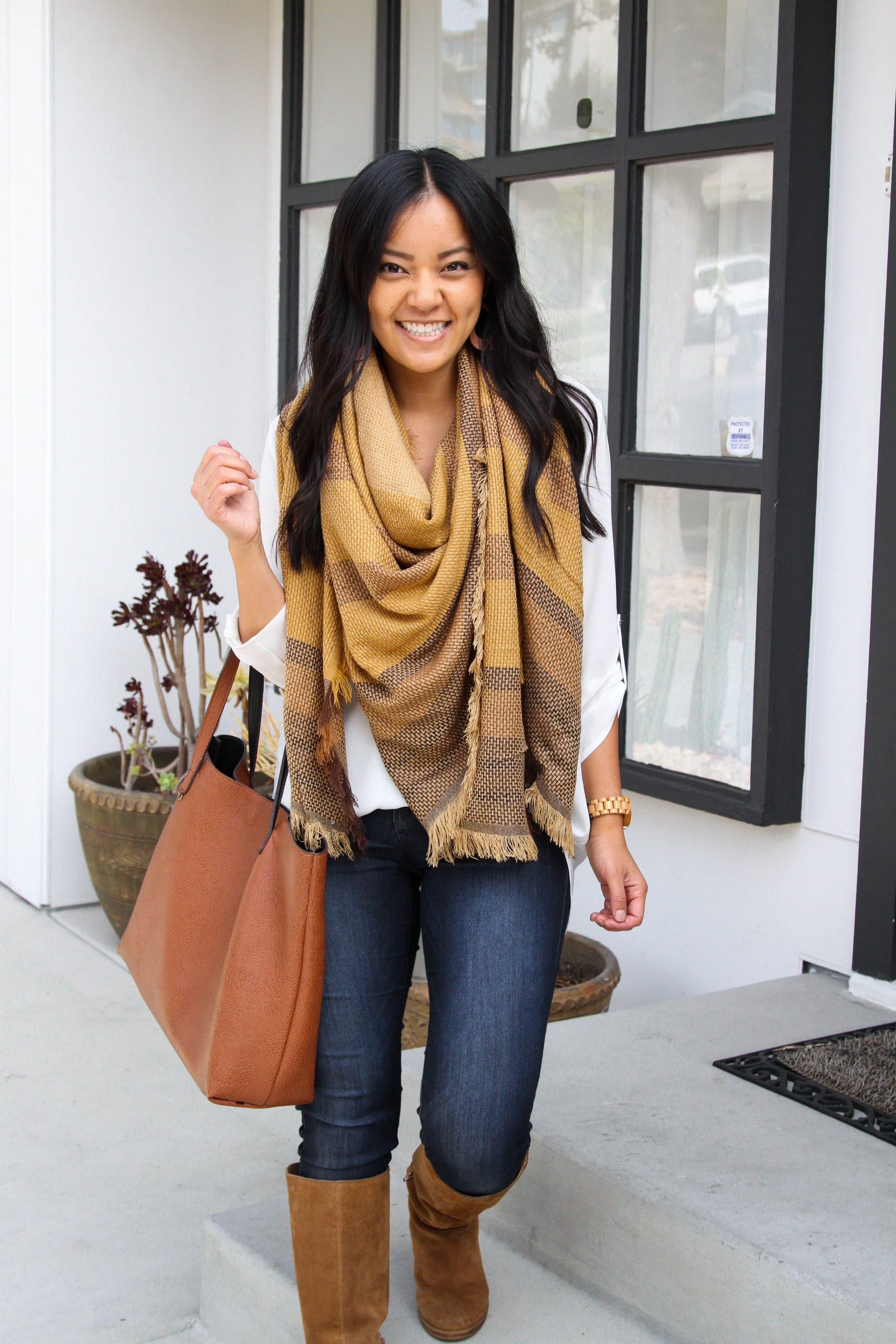 cognac bag + white tunic + yellow blanket scarf + skinny jeans + suede boots