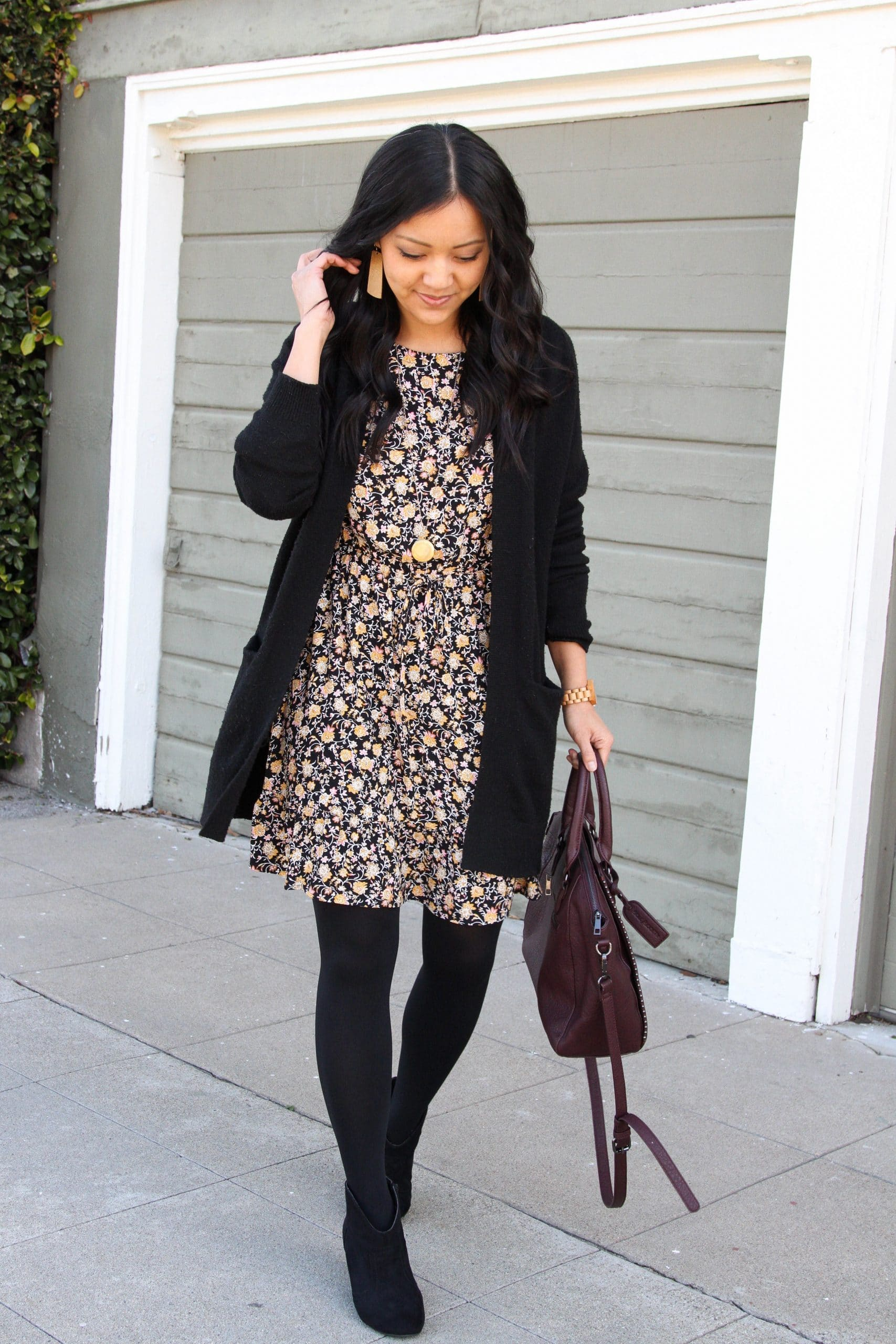 Winter Dress Outfit: floral print dress + black cardigan + black tights + black suede booties + maroon bag + long gold circle pendant necklace + tan leather earrings