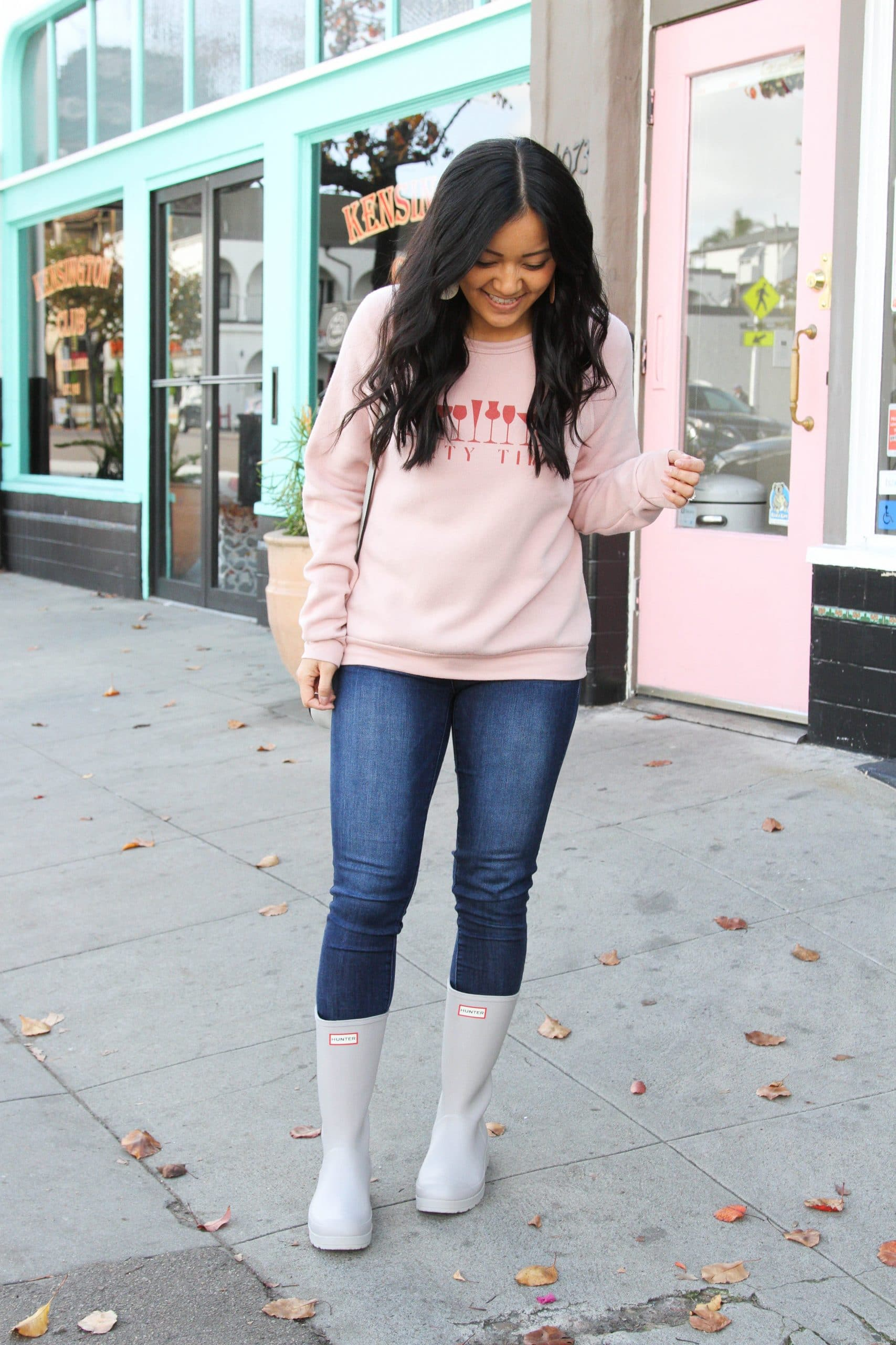 grey purse + pink sweatshirt + skinny jeans + grey rain boots