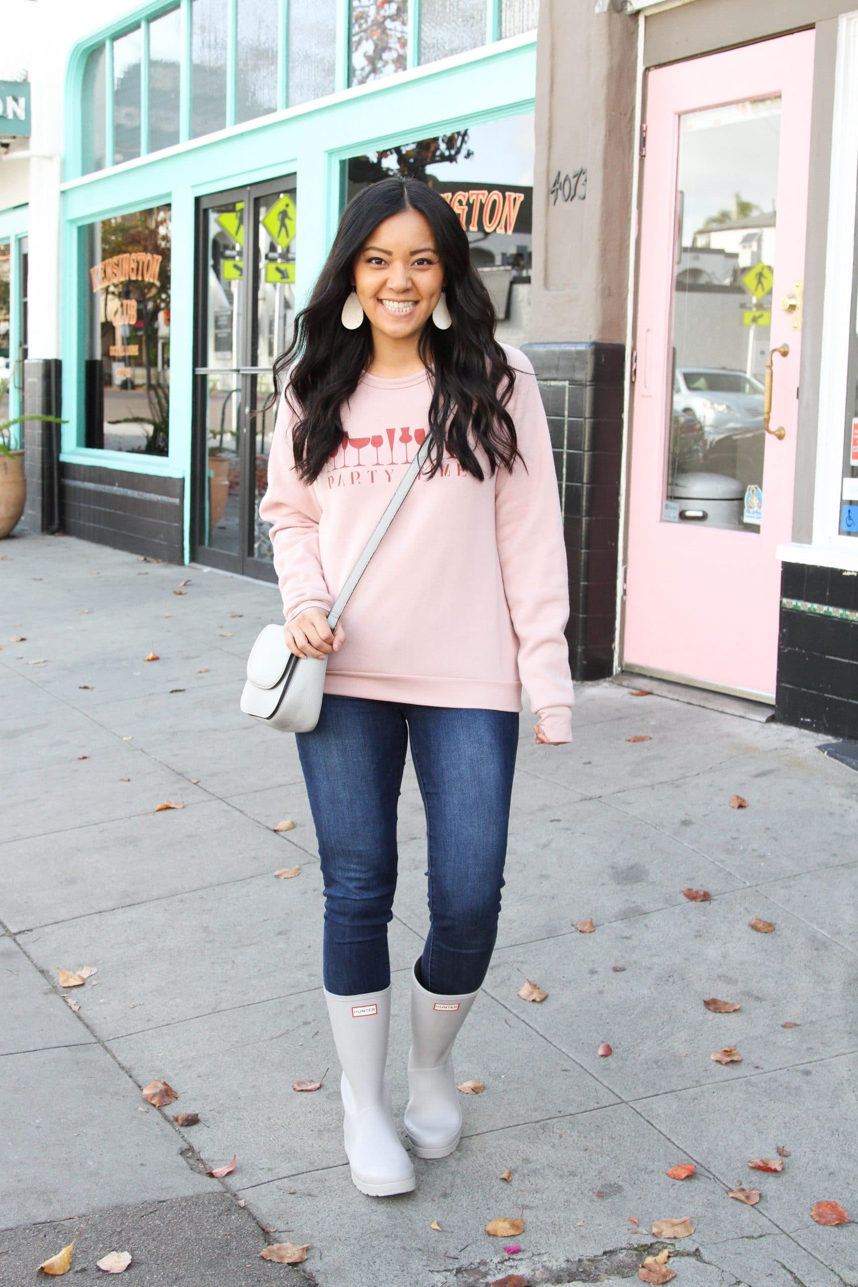 Casual Winter Outfit: pink graphic sweatshirt + skinny jeans + grey tall rain boots + grey crossbody bag + white cork leather earrings