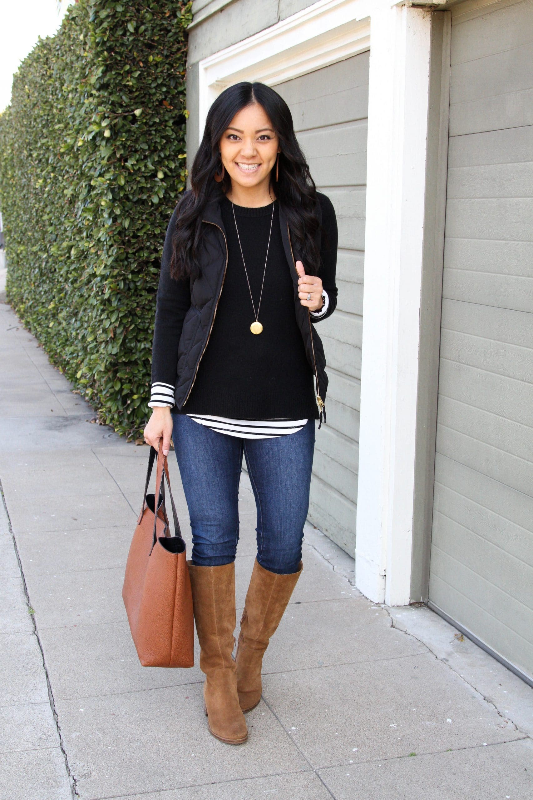 Winter Casual Outfit: long sleeve striped tee + black sweater + black quilted vest + skinny jeans + tan suede boots + cognac tote + long gold circle pendant necklace + tan leather earrings