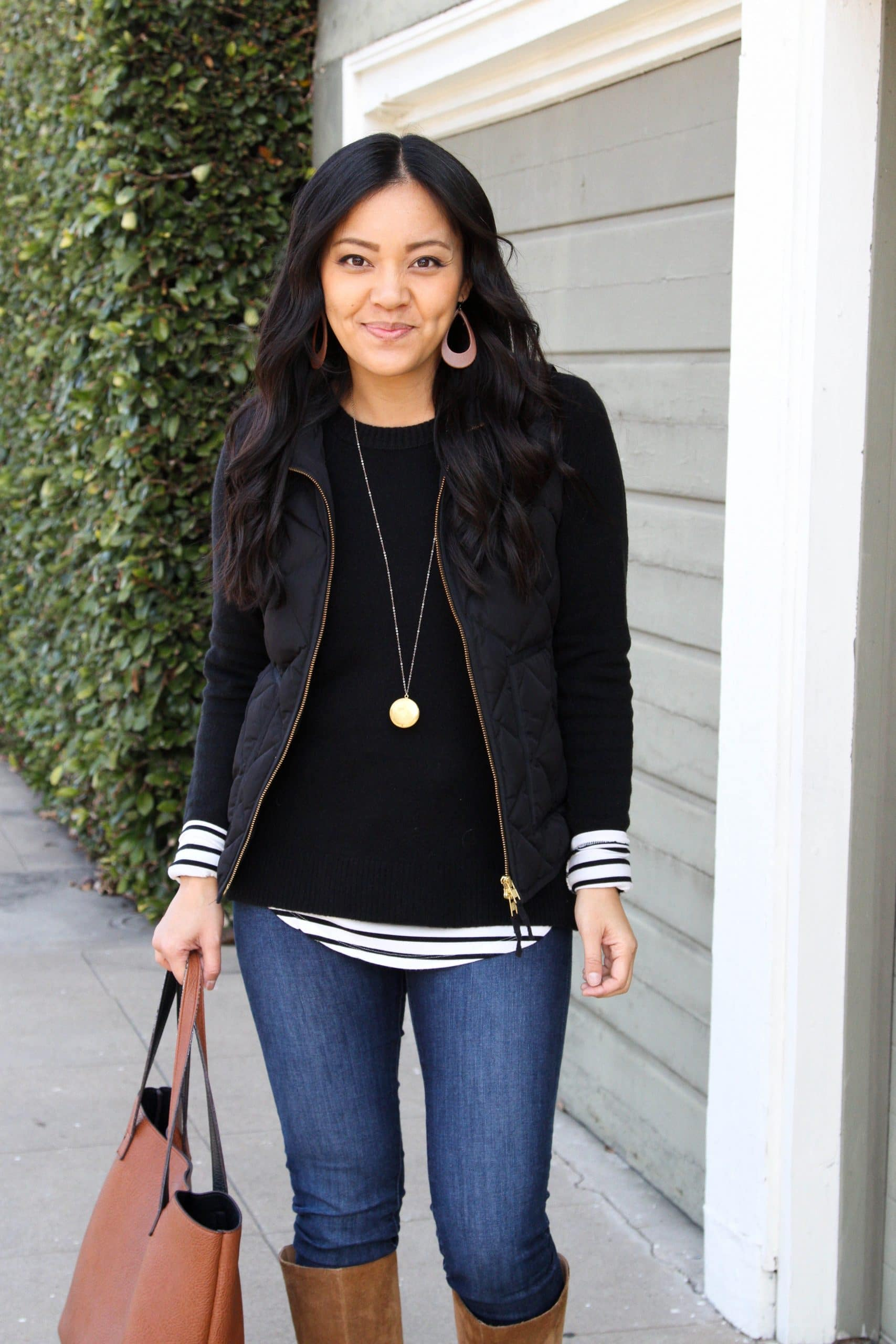 Winter Layering Outfit: black quilted vest + striped tee + black crewneck sweater + skinny jeans + cognac suede boots + gold pendant necklace + cognac tote