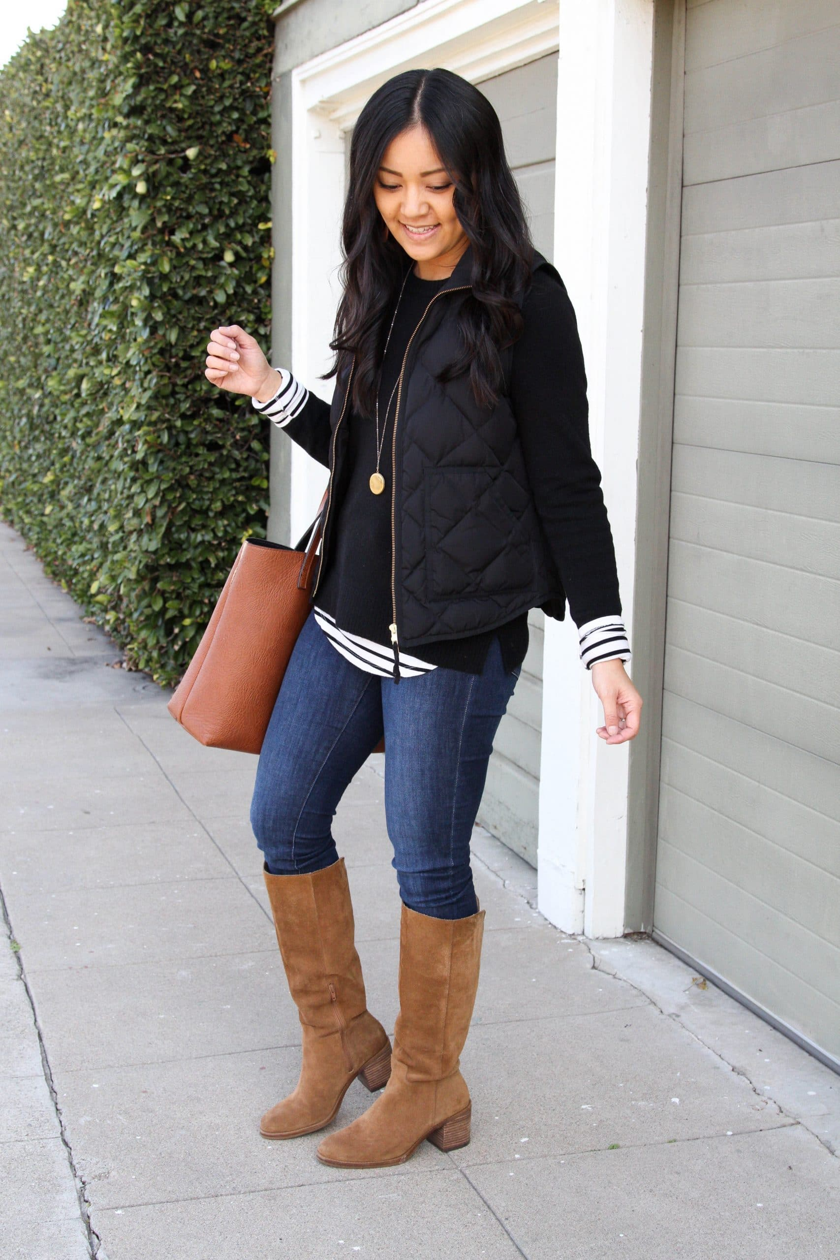 Winter Layering Outfit: black crewneck sweater + black quilted vest + striped tee + cognac suede boots + skinny jeans + cognac tote + gold pendant necklace