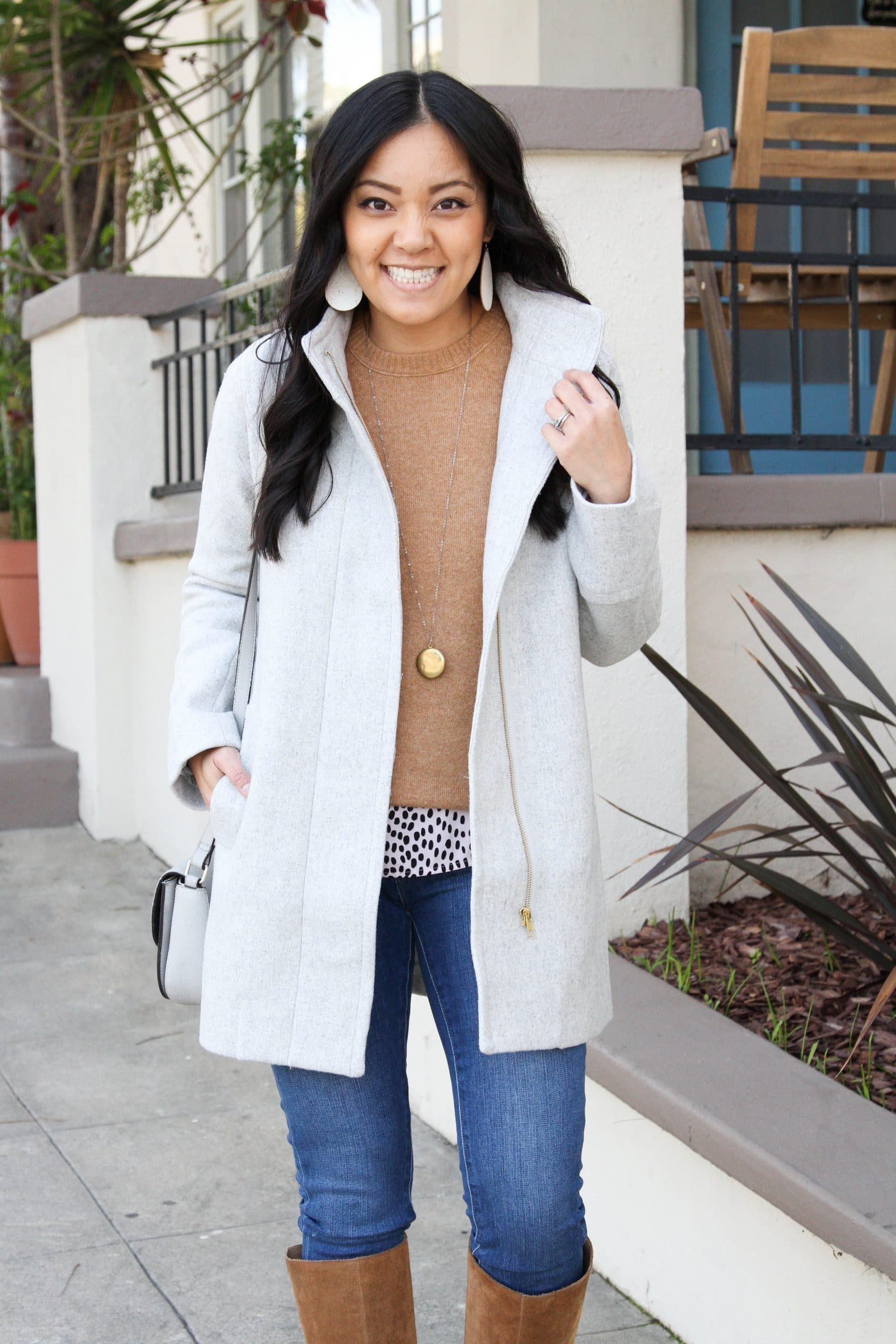 Winter Coat Layering Outfit: cream wool coat + tan crewneck sweater + animal print top + skinny jeans + cognac suede boots + gray bag + gold pendant necklace