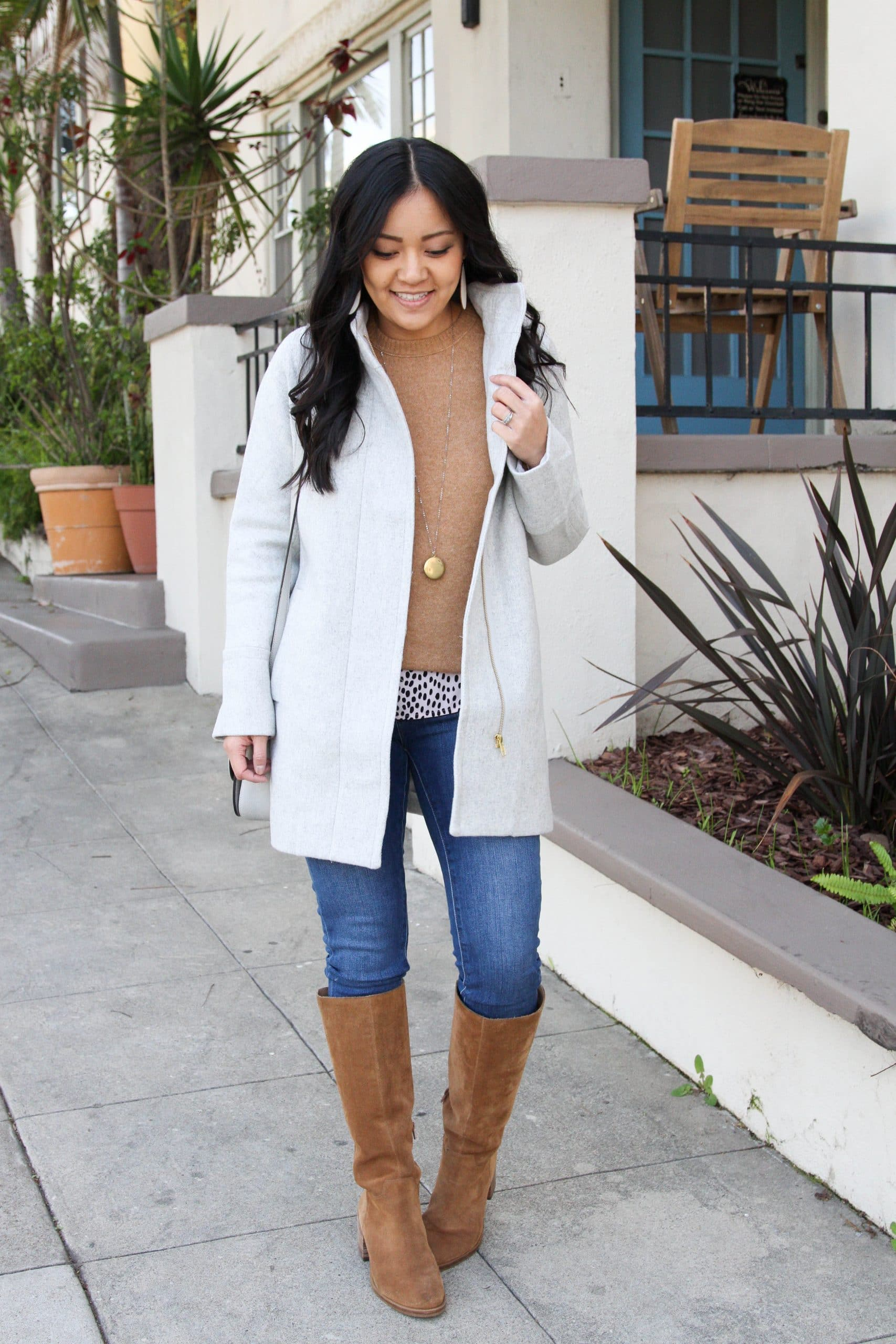 Winter Coat Layering Outfit: tan crewneck sweater + animal print top + cream wool coat + skinny jeans + cognac suede boots + gold pendant necklace + gray bag