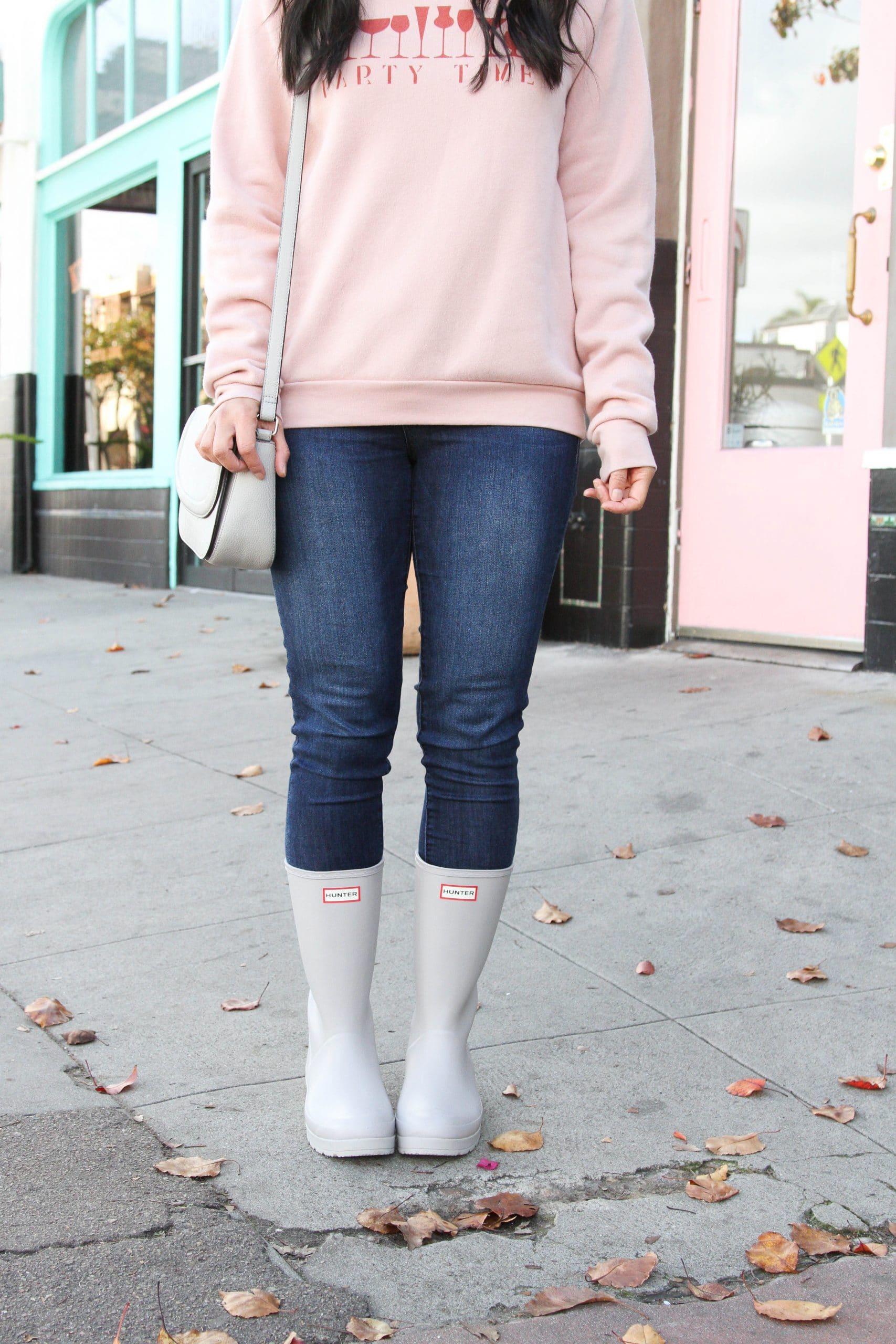 pink sweatshirt + skinny jeans + grey purse + grey rain boots