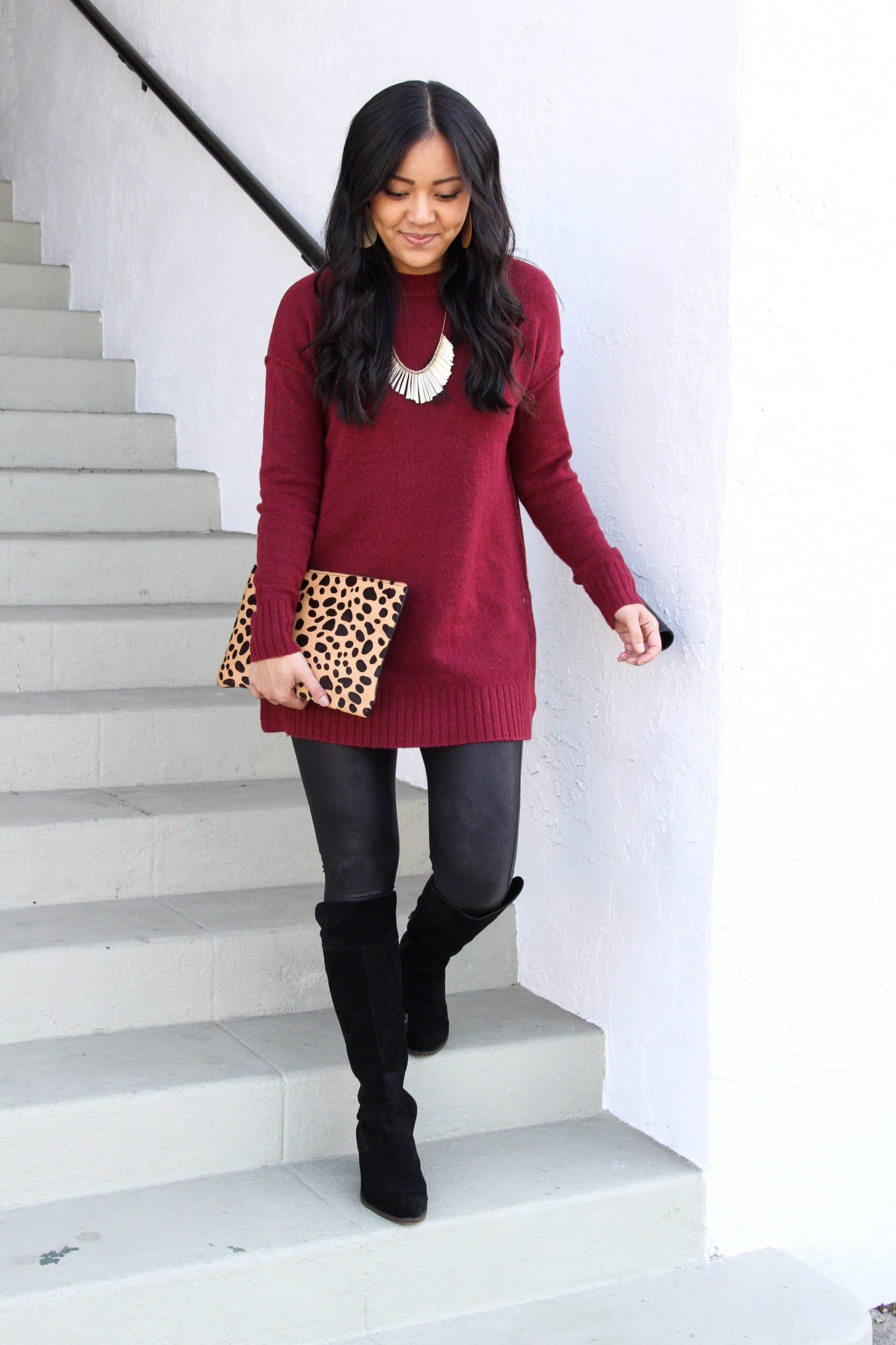 maroon sweater + black boots + faux leather leggings + leopard print clutch