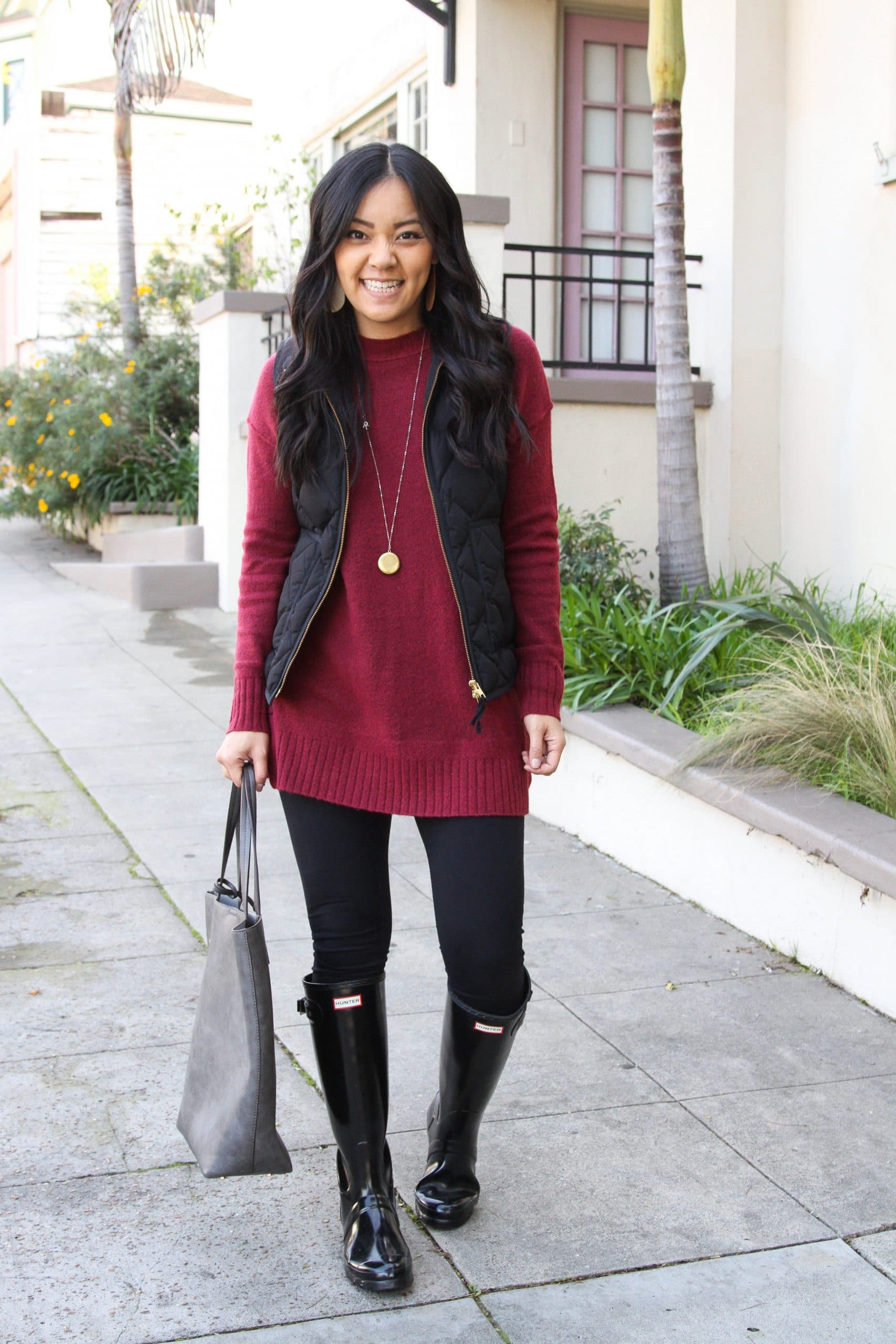 Winter Leggings Outfit: maroon tunic sweater + black leggings + black quilted vest + black rain boots + gray tote + gold pendant necklace + gold leather earrings