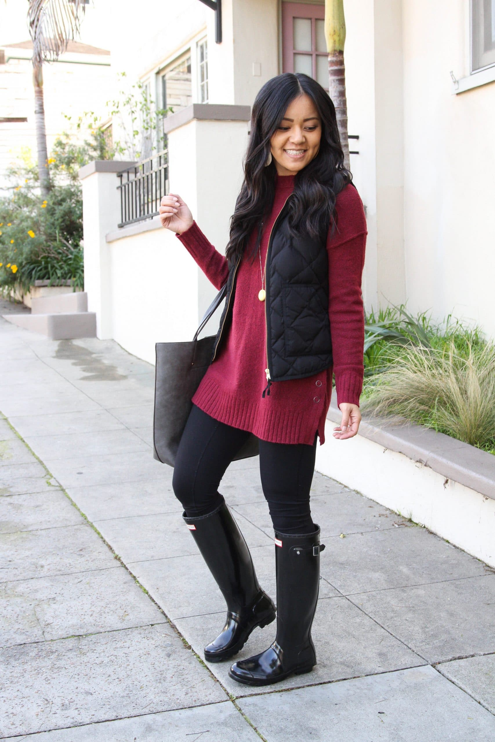 Winter Leggings Outfit: black leggings + maroon tunic sweater + black rain boots + black quilted vest + gold leather earrings + gray tote + gold pendant necklace