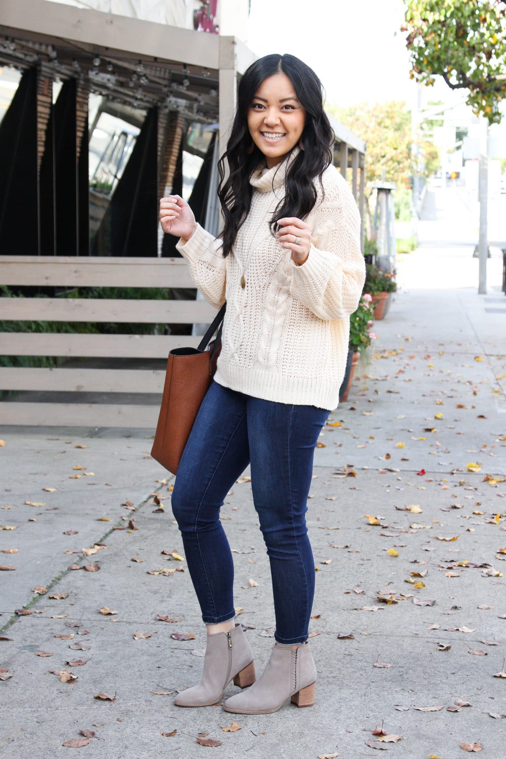 cream cable knit sweater + taupe booties + skinny jeans + cognac tote