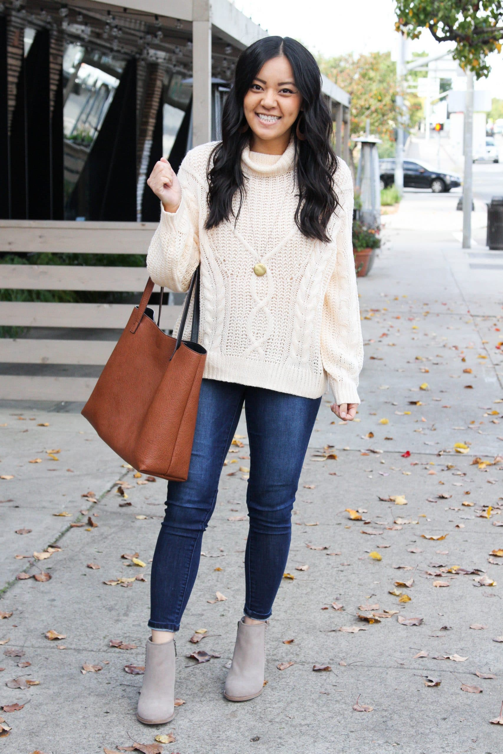 cream cable knit sweater + skinny jeans + taupe booties + cognac tote