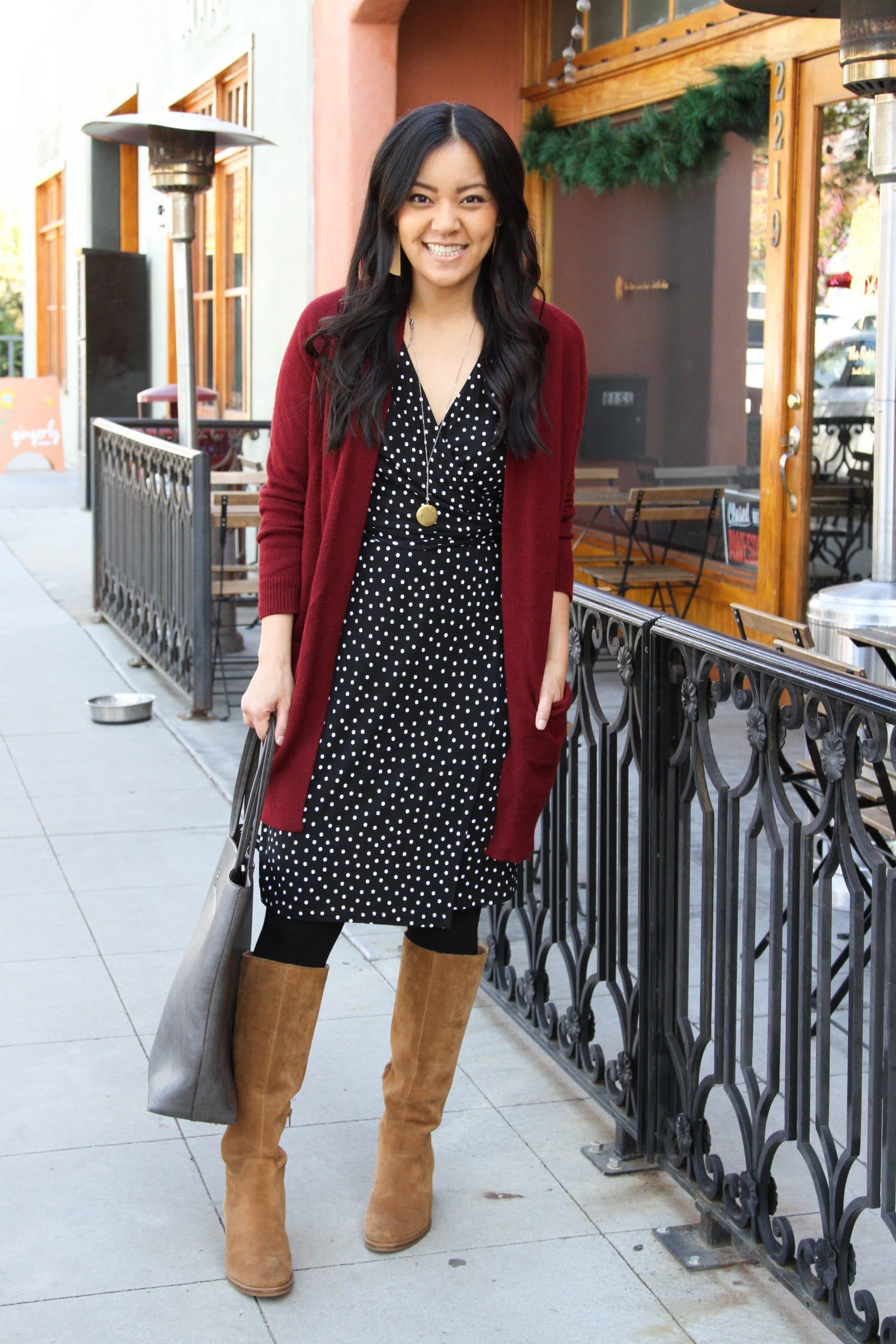 Winter Dress Outfit: black and white spotted dress + red cardigan + black tights + tan suede boots + grey tote + long gold circle pendant necklace + tan leather earrings
