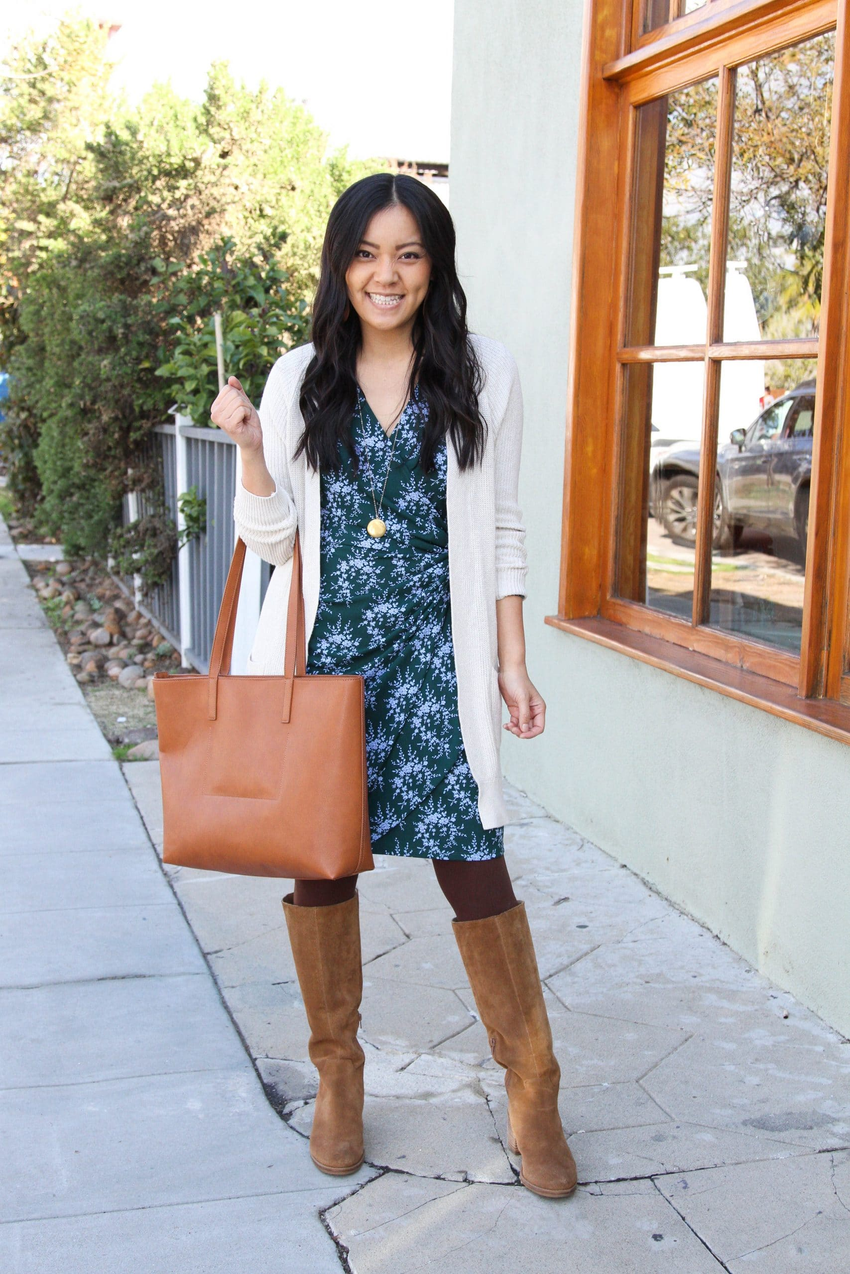Winter Business Casual Dress Outfit: blue and green wrap dress + cream long cardigan + brown tights + cognac suede boots + cognac tote + gold pendant necklace