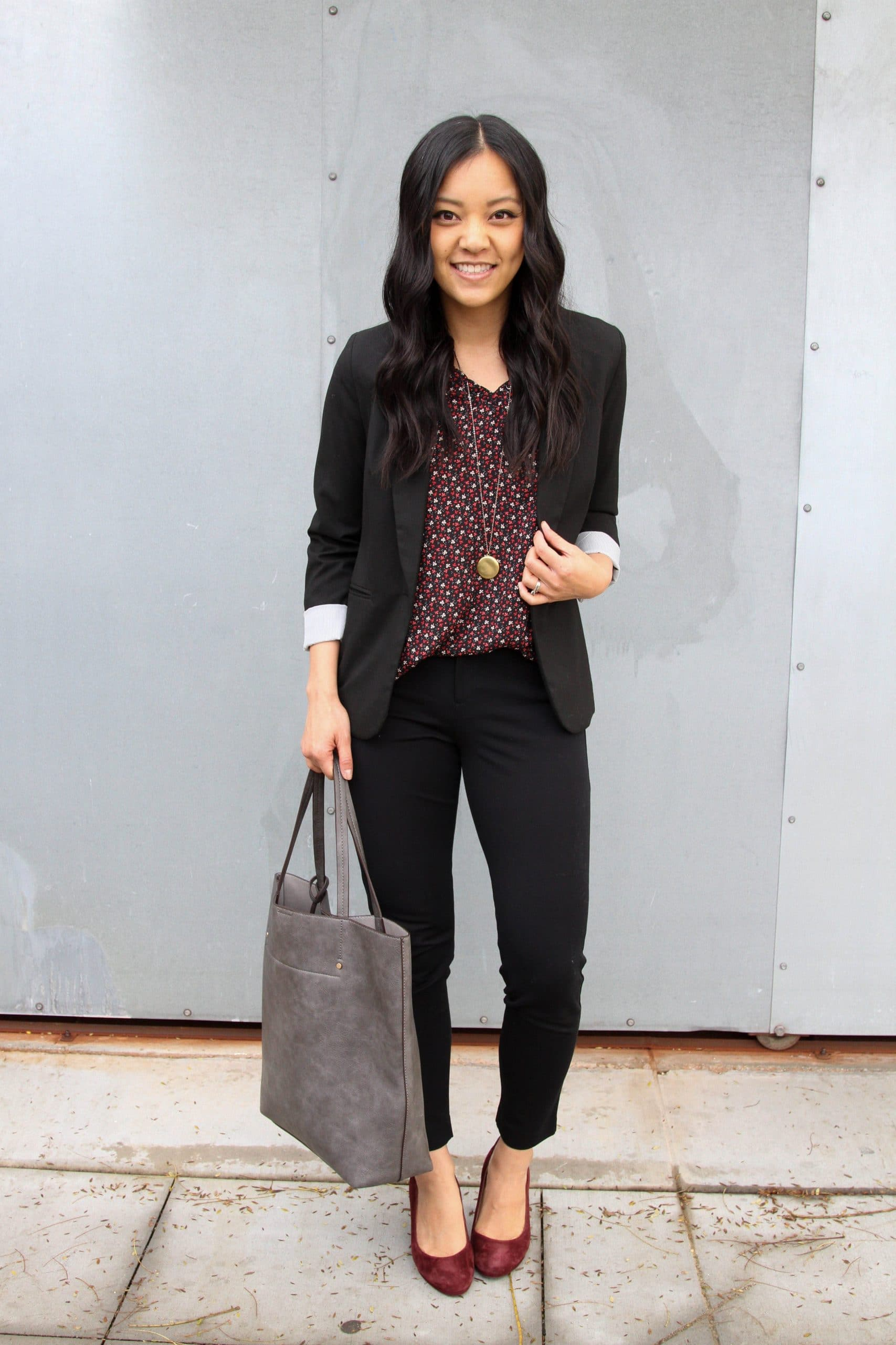 Business Casual Outfit: floral v-neck top + black blazer + black skinny pants + maroon suede pumps + gray leather tote bag + long gold disc pendant