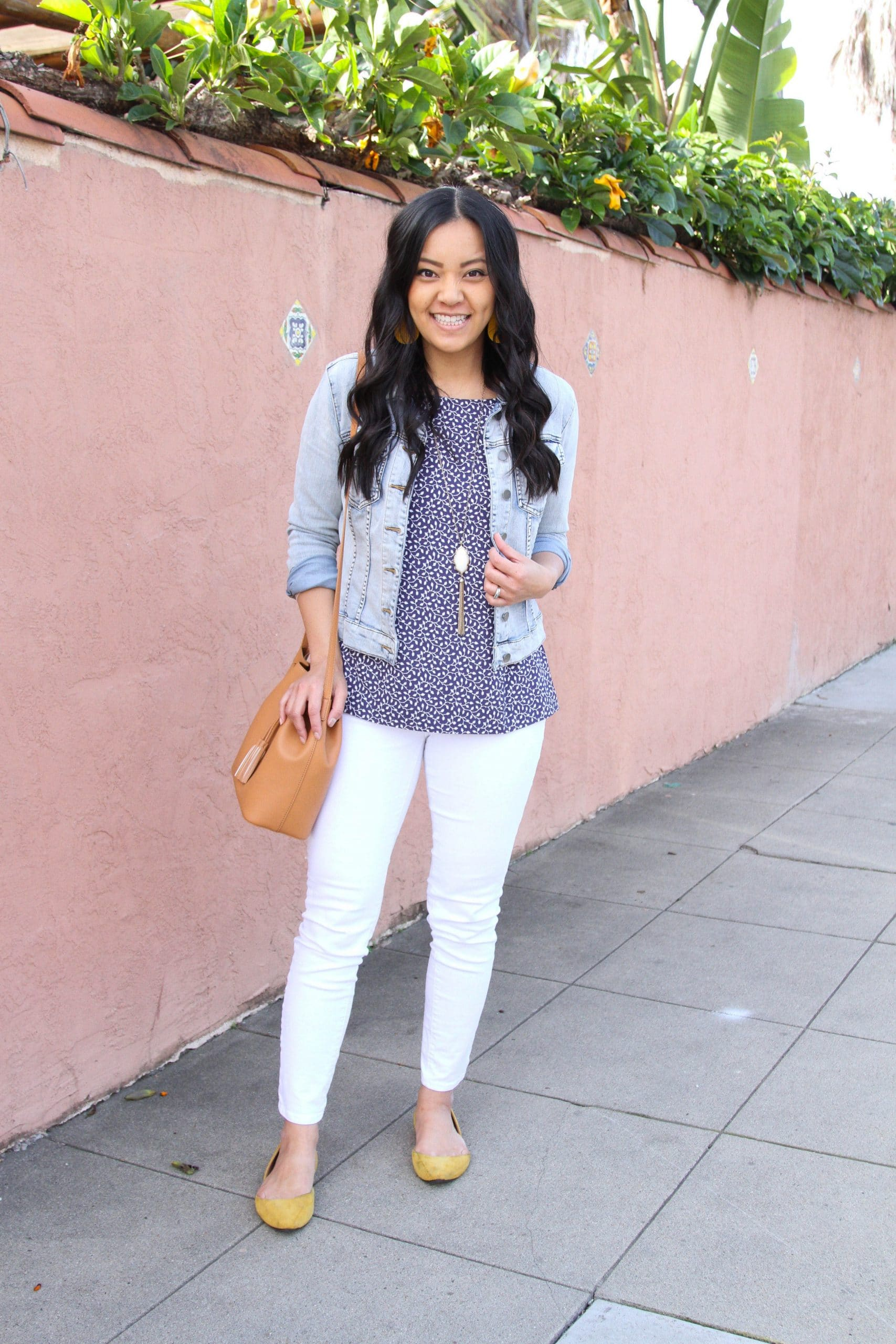White Jeans Outfit: navy printed blouse + white skinny jeans + yellow faux suede flats + denim jacket + long gold fringe pendant necklace + yellow leather earrings + tan faux leather drawstring crossbody bag