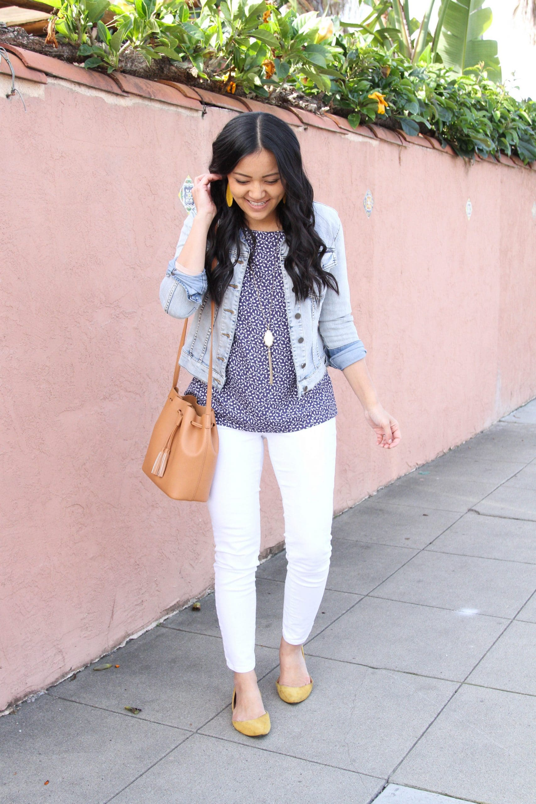 White Jeans Outfit: navy printed blouse + white skinny jeans + denim jacket + yellow faux suede flats + tan faux leather drawstring crossbody bag + long gold fringe pendant necklace + yellow leather earrings