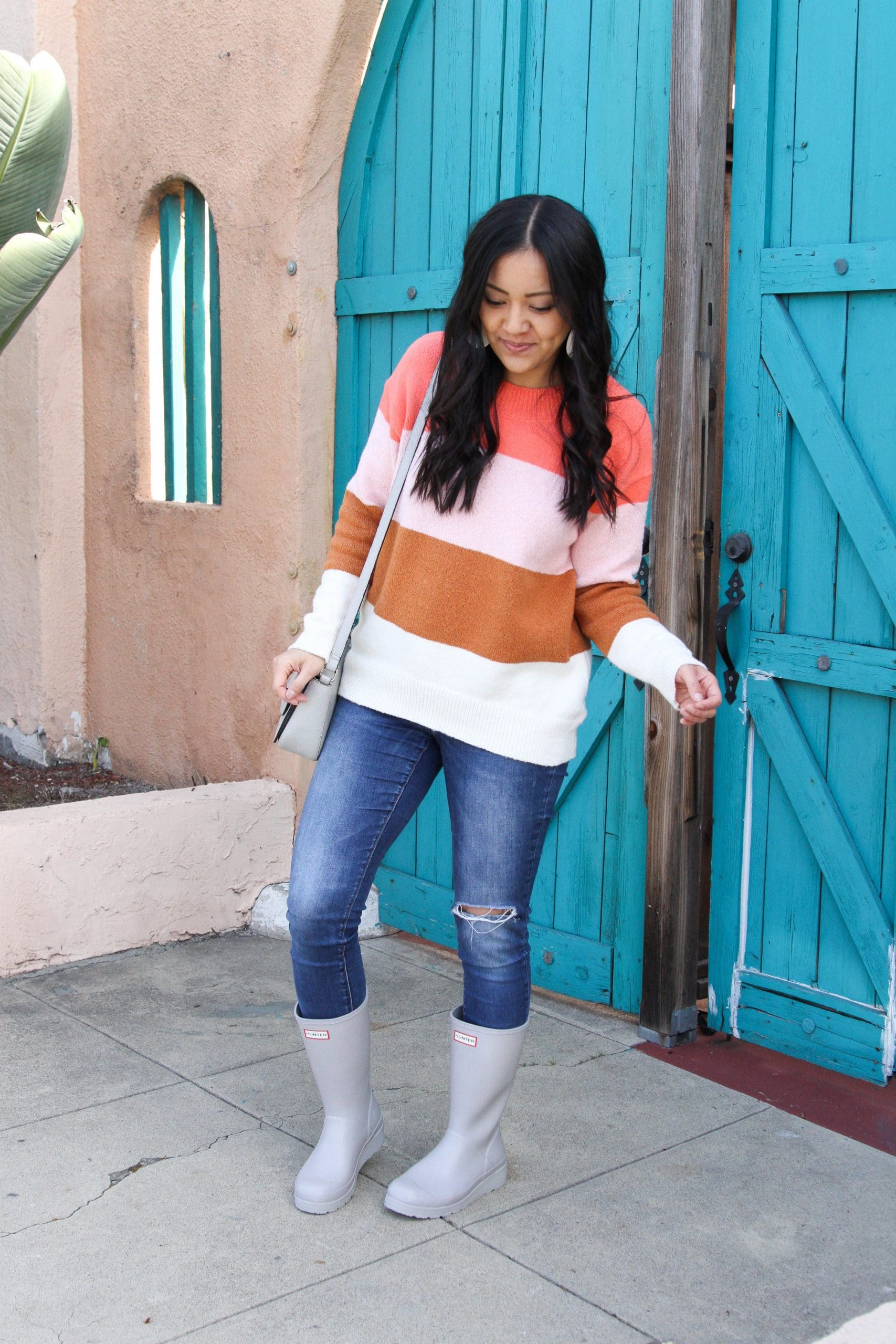 Casual Winter Outfit: distressed skinny jeans + pink colorblock sweater + grey crossbody bag + grey tall rain boots + white leather earrings