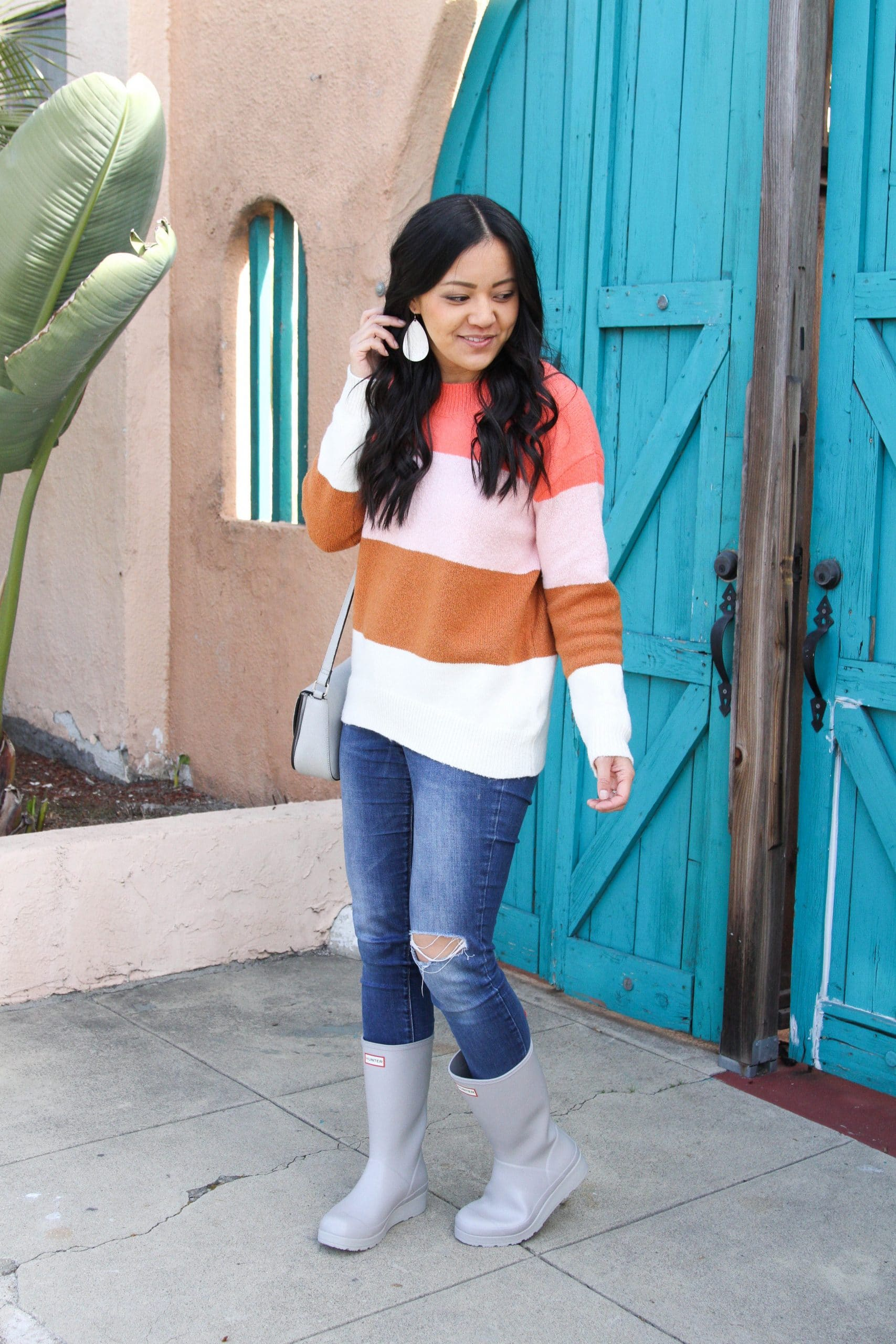 Casual Winter Outfit: pink colorblock sweater + distressed skinny jeans + grey crossbody bag + grey tall rain boots + white leather earrings