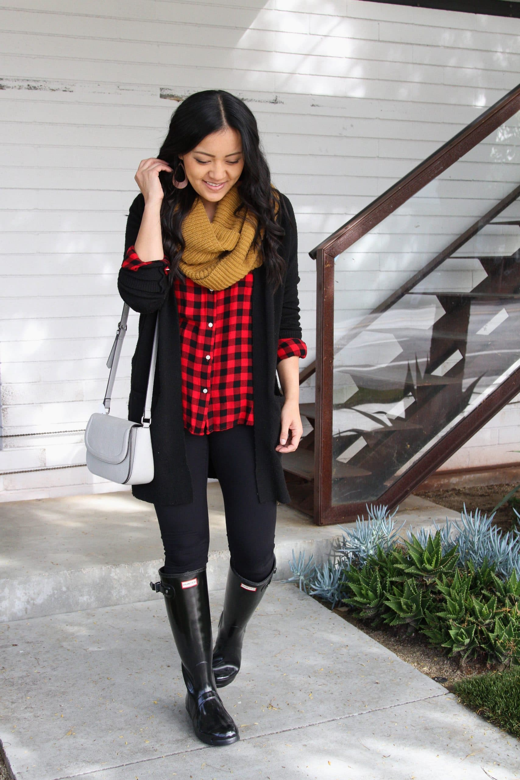 Winter Leggings Outfit: red buffalo plaid shirt + black leggings + black cardigan + black rain boots + mustard infinity scarf + gray crossbody purse + brown leather earrings