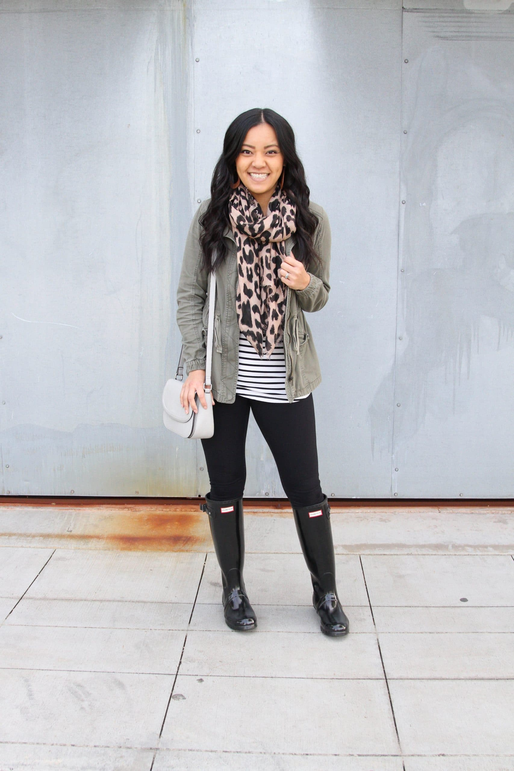 Winter Leggings Outfit: striped tee + black leggings + olive utility jacket + black rain boots + leopard scarf + gray crossbody bag + brown leather earrings