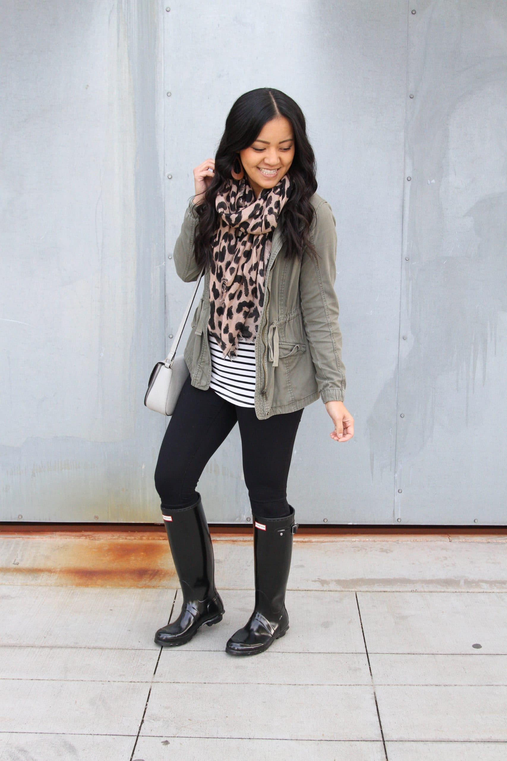 Winter Leggings Outfit: black leggings + striped tee + black rain boots + olive utility jacket + brown leather earrings + leopard scarf + gray crossbody bag