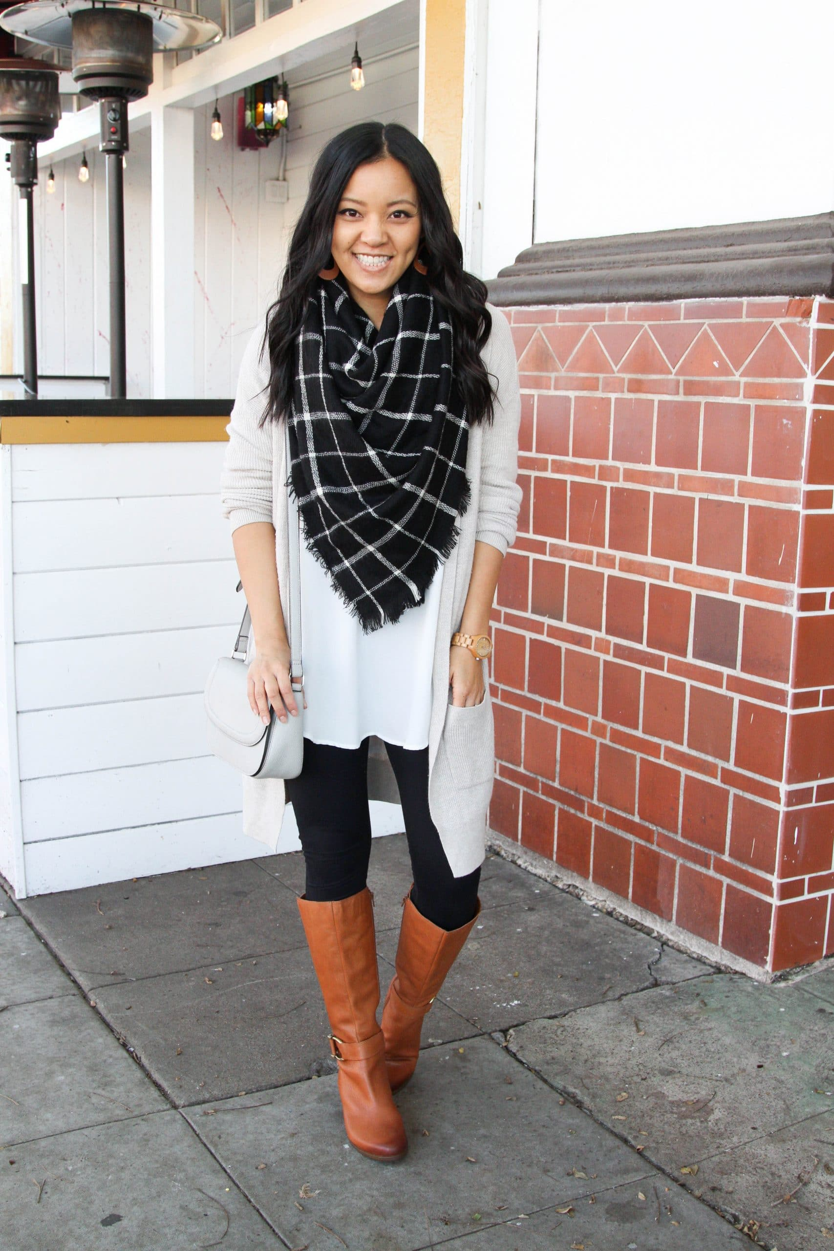 Winter Leggings Outfit: white tunic + black leggings + cream long cardigan + black and white plaid blanket scarf + cognac tall boots + grey crossbody bag + brown leather earrings