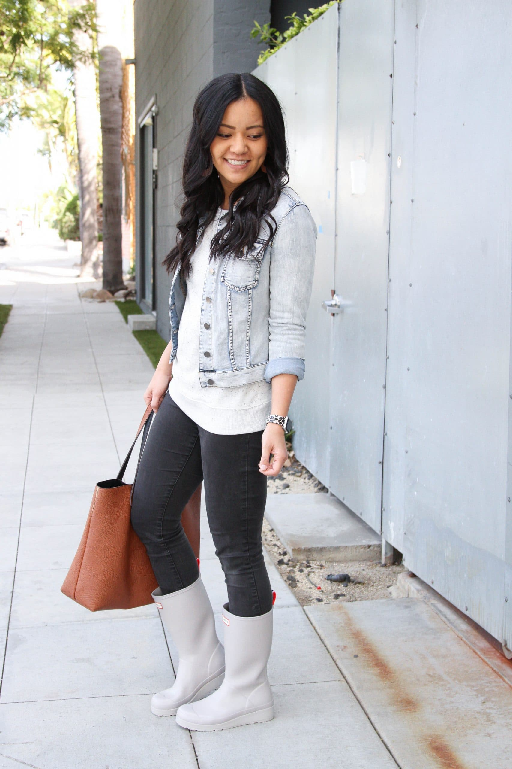 Casual Winter Outfit: black skinny jeans + grey speckled sweatshirt + grey tall rain boots + denim jacket + tan cutout leather earrings + cognac tote bag
