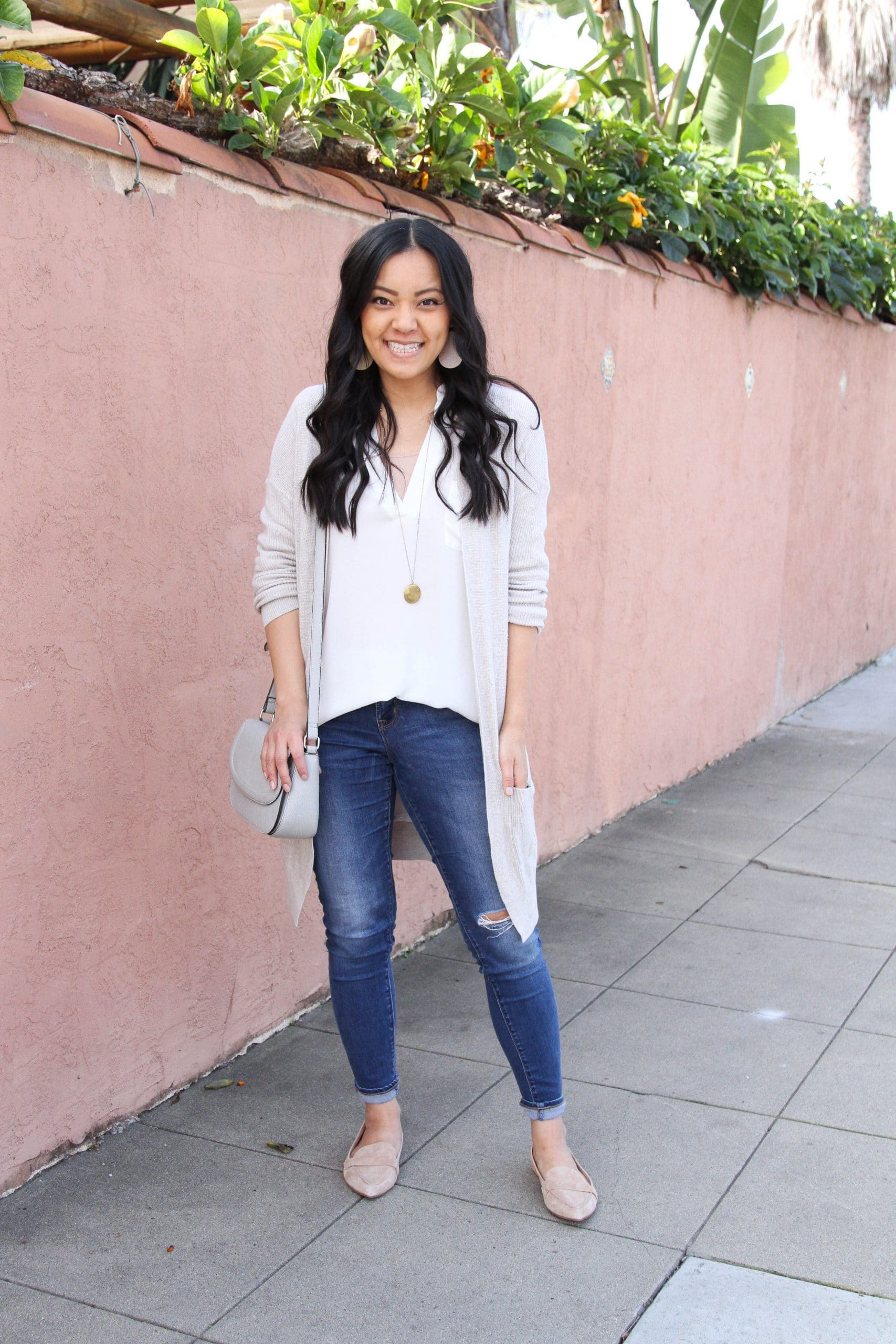 Transitional Winter To Spring Skinny Jeans Outfit: distressed skinny jeans + white tunic + nude loafers + cream long cardigan + blush leather earrings + long gold disc pendant necklace + grey crossbody bag