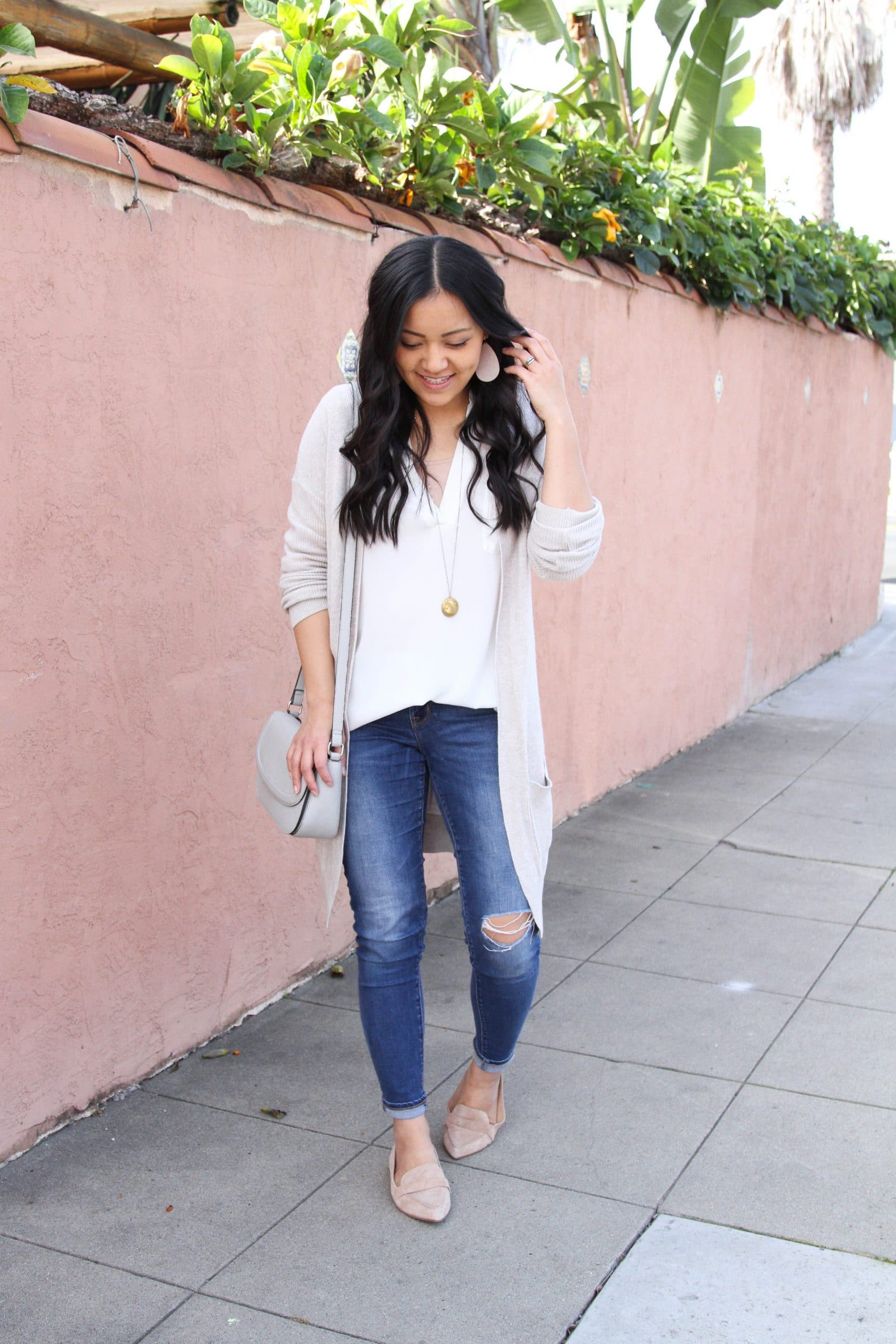 Transitional Winter to Spring Skinny Jeans Outfit: white tunic + distressed skinny jeans + cream long cardigan + nude loafers + long gold disc pendant necklace + grey crossbody bag + blush leather earrings