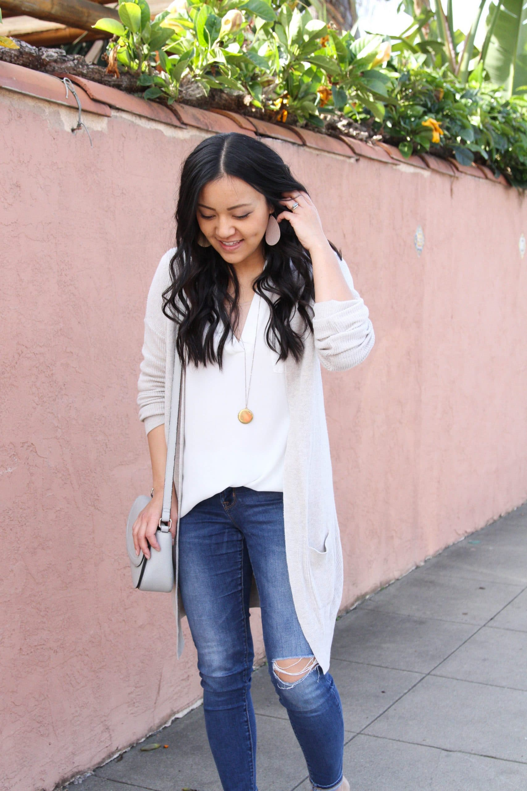 Transitional Winter To Spring Skinny Jeans Outfit: white tunic + distressed skinny jeans + nude loafers + cream long cardigan + grey crossbody bag + blush leather earrings + long gold disc pendant necklace