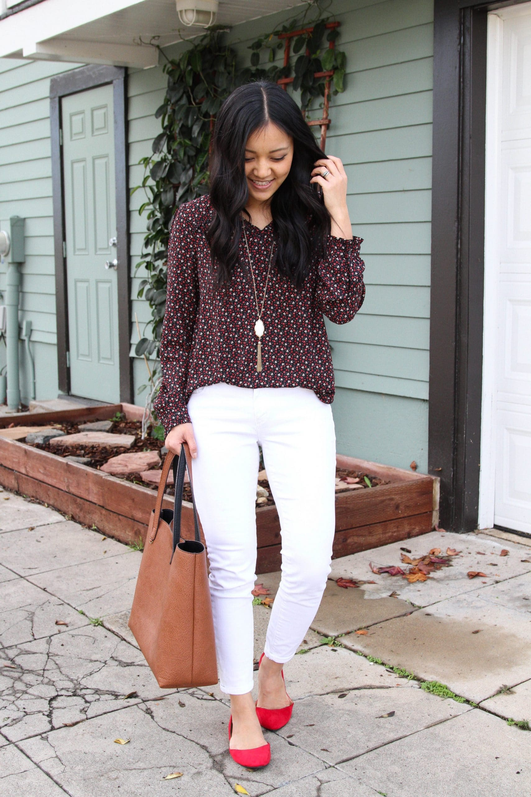 White Jeans Outfit: floral long-sleeve v-neck top + white skinny jeans + red faux suede flats + cognac tote bag + long gold fringe pendant necklace