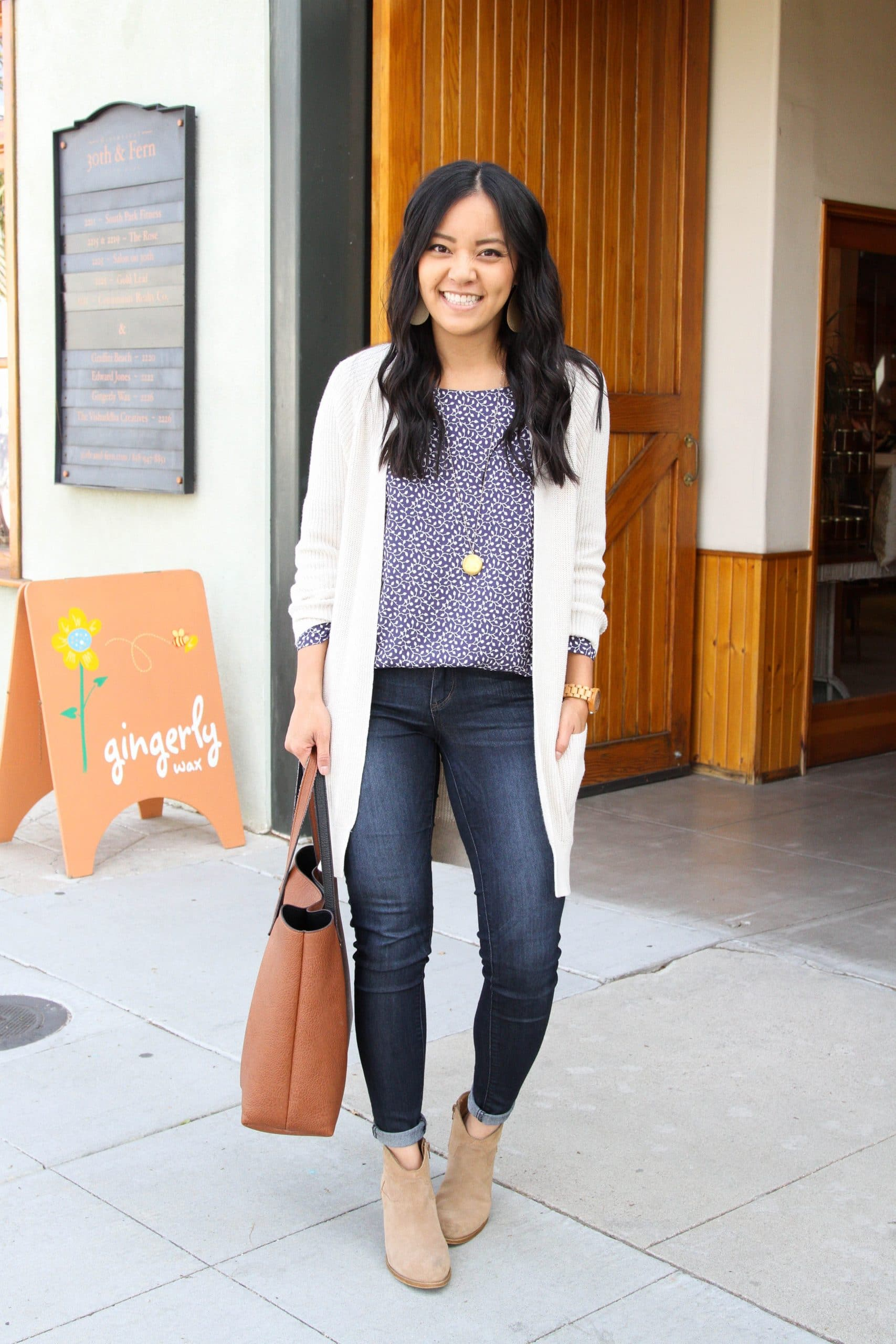 Winter to Spring Transitional Outfit: navy printed blouse + skinny jeans + long cream cardigan + tan suede booties + cognac leather tote bag + long gold disc pendant necklace + gold leather earrings