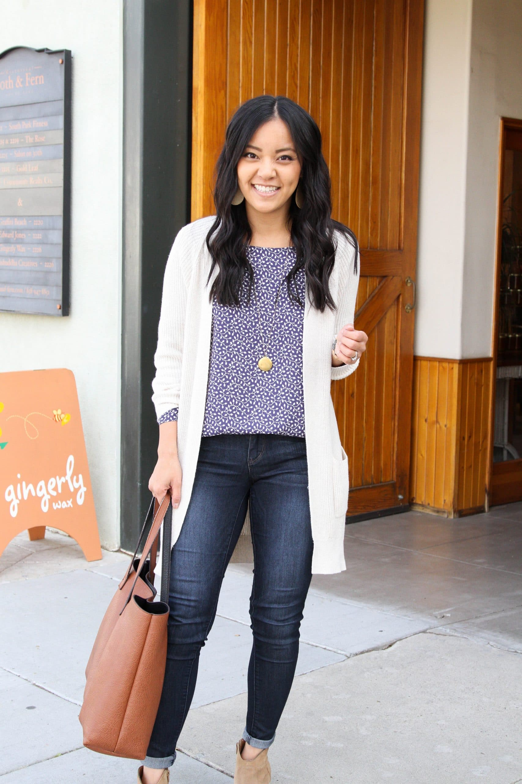 Winter to Spring Transitional Outfit: skinny jeans + navy printed blouse + tan suede booties + long cream cardigan + gold leather earrings + cognac leather tote bag + long gold disc pendant necklace