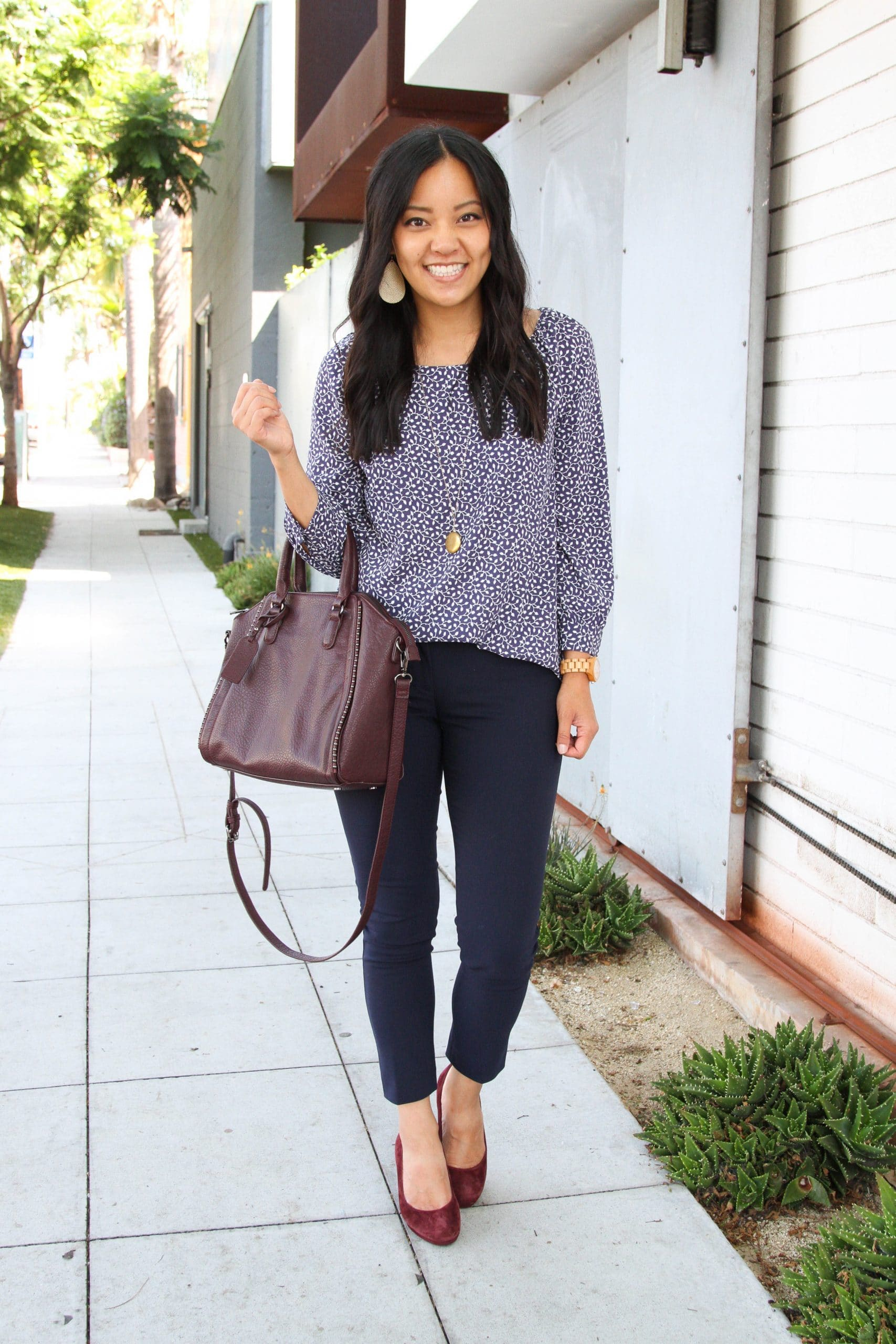 Business Casual Outfit: navy printed blouse + navy skinny ankle pants + maroon suede heels + maroon leather satchel + long gold disc pendant necklace + gold leather earrings