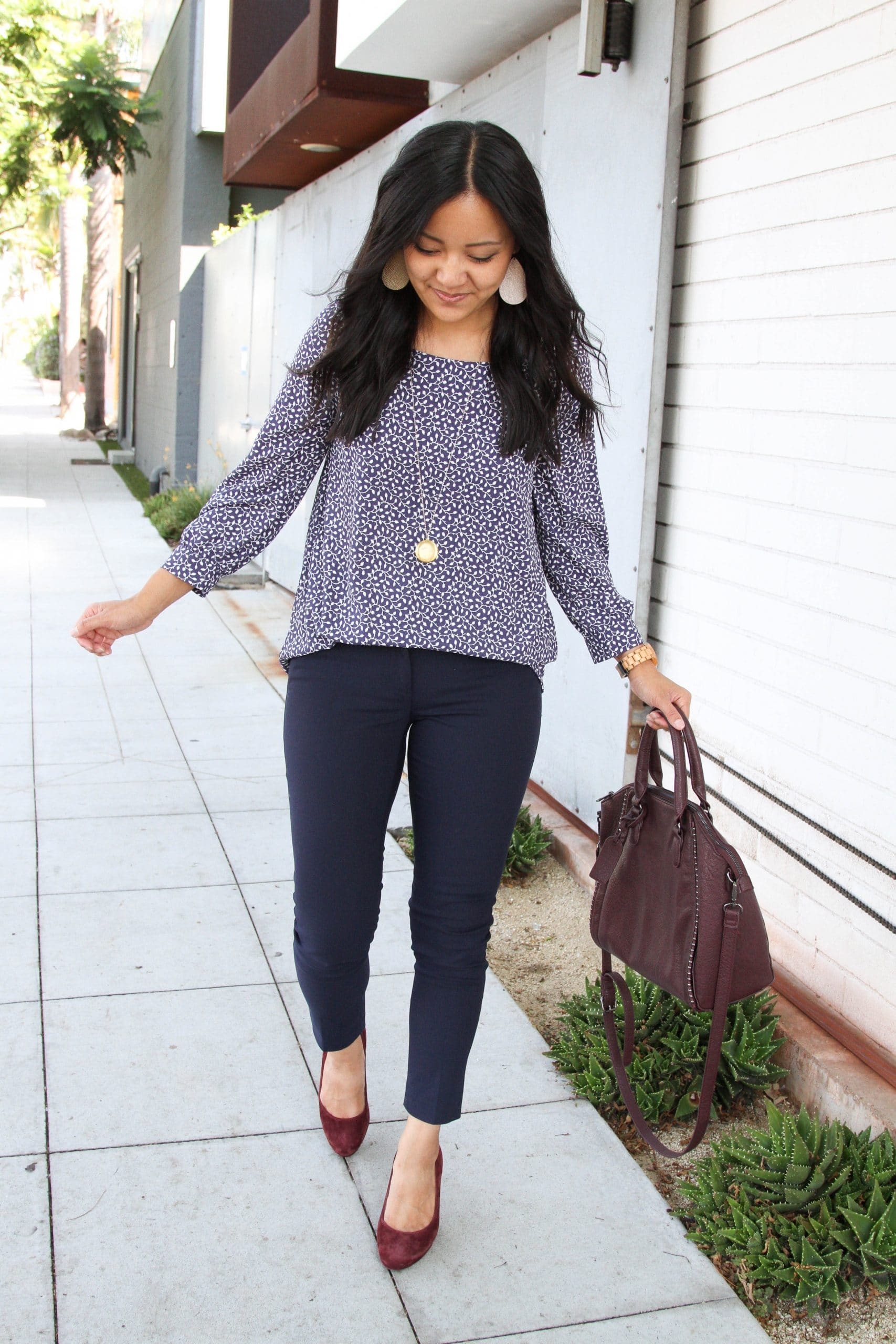 Business Casual Outfit: navy skinny ankle pants + navy printed blouse + maroon leather satchel + maroon suede heels + gold leather earrings + long gold disc pendant necklace