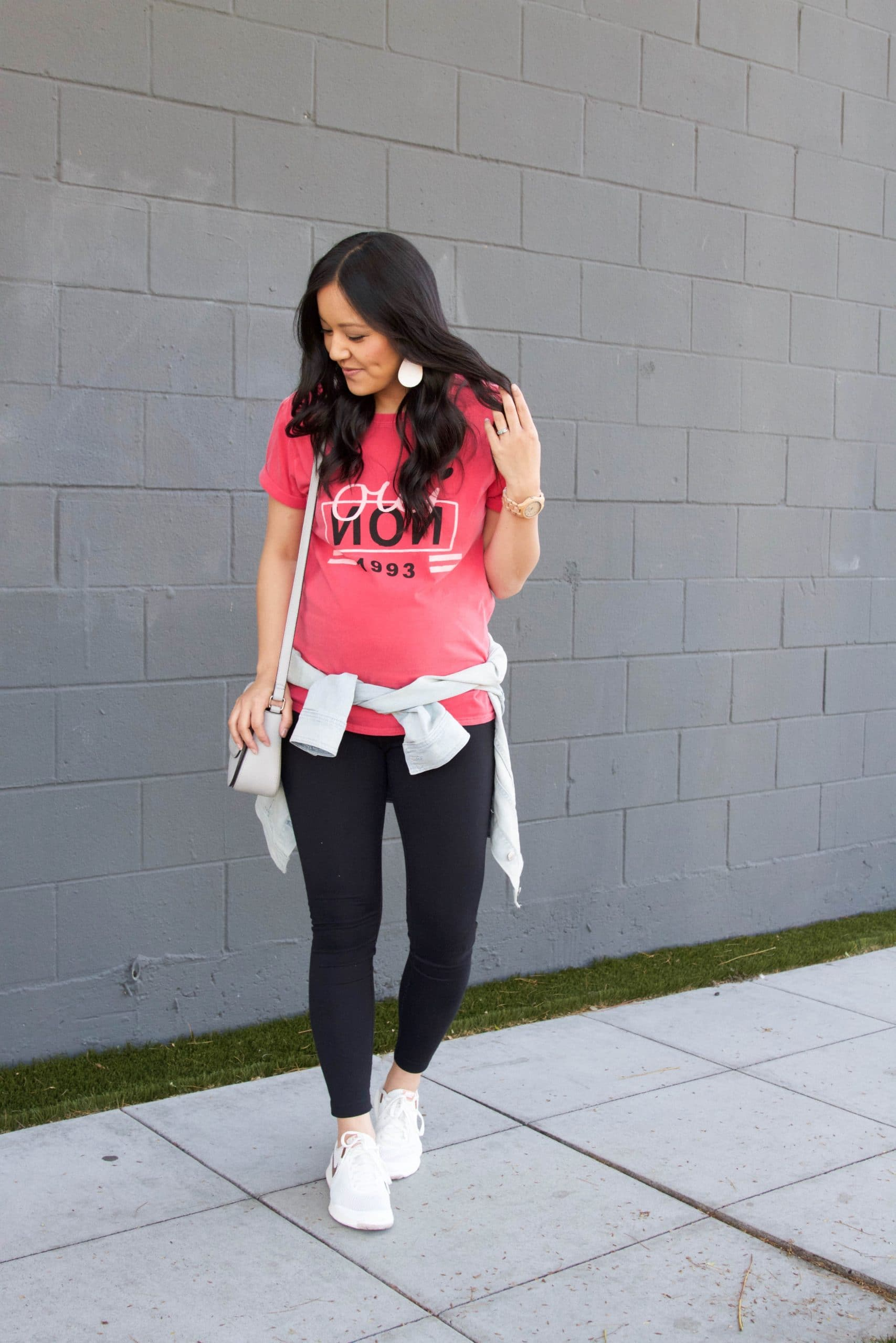 Casual Leggings Outfit: hot pink graphic tee + black leggings + denim jacket + white sneakers + grey crossbody bag + blush leather earrings