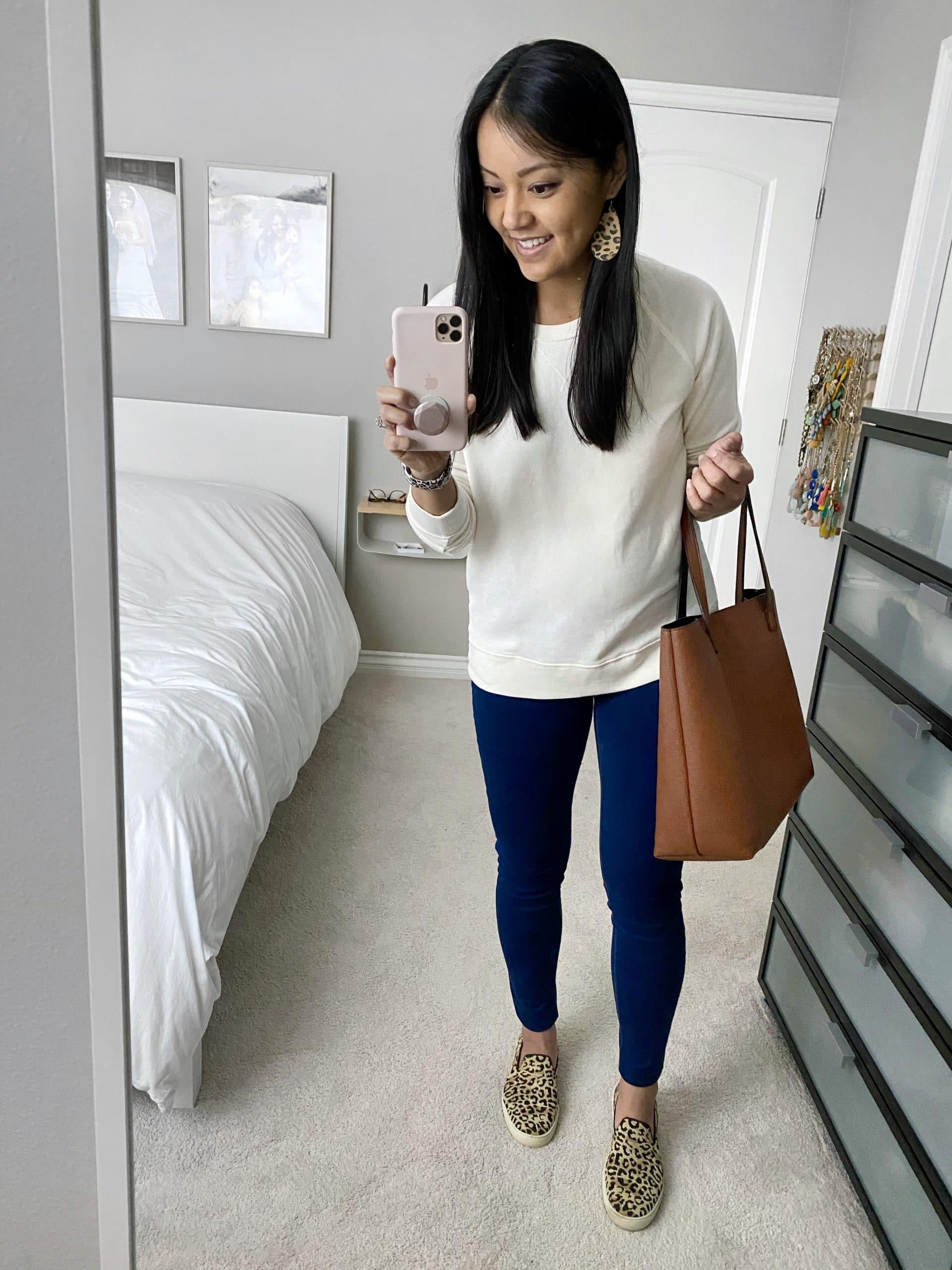 Casual Spring Outfit: cream pullover sweatshirt + dark skinny jeans + leopard slip-on sneakers + cognac tote bag + leopard leather earrings