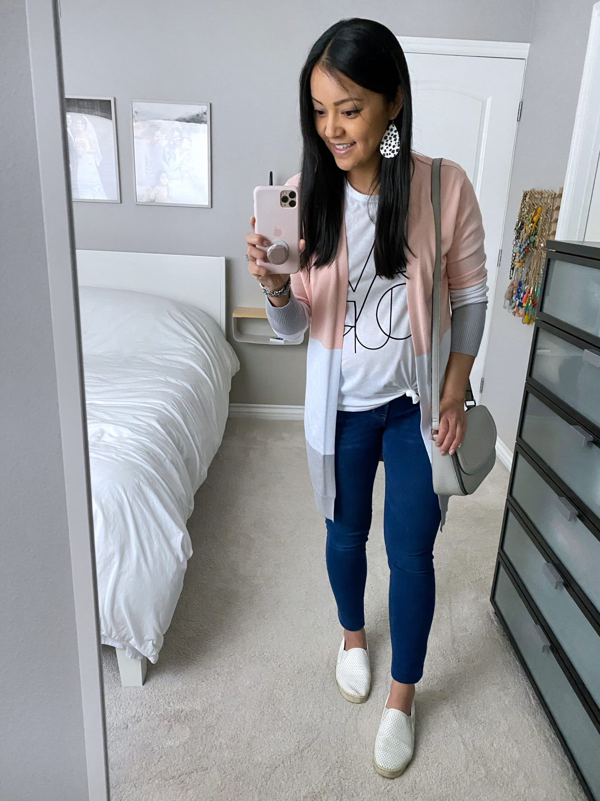 Casual Spring Outfit: white graphic tee + pink color block cardigan + skinny jeans + white slip on sneakers + grey crossbody bag + spotted leather earrings