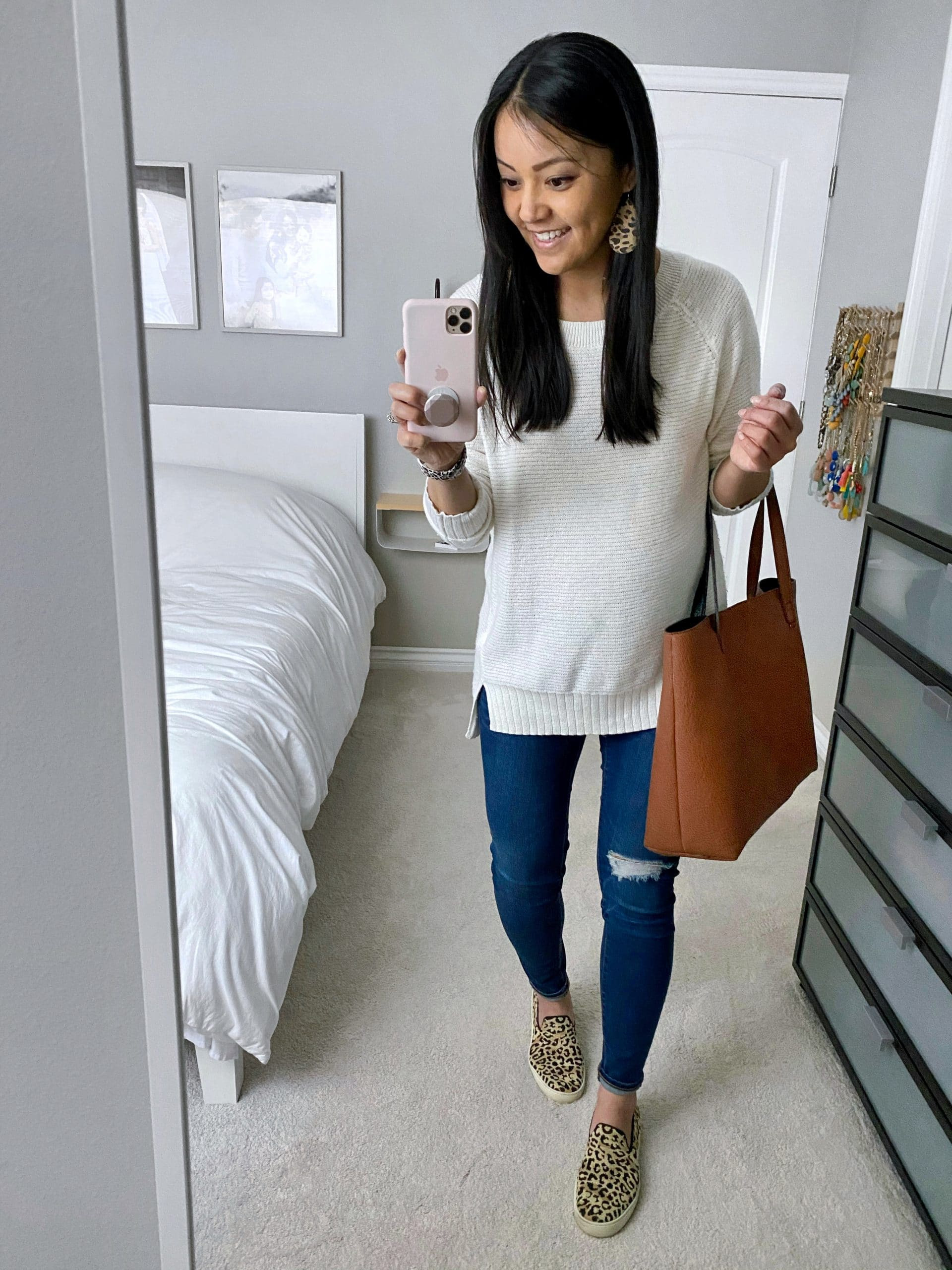 Casual Spring Outfit: white crewneck sweater + distressed skinny jeans + leopard print sneakers + cognac tote + leopard leather earrings