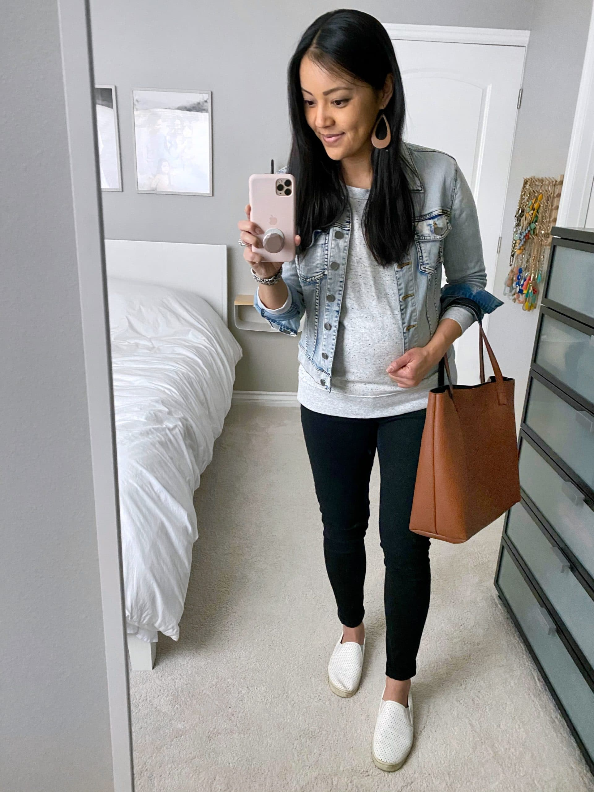 Casual Spring Outfit: speckled sweatshirt + denim jacket + black skinny jeans + white slip on sneakers + cognac tote + tan leather cutout earrings