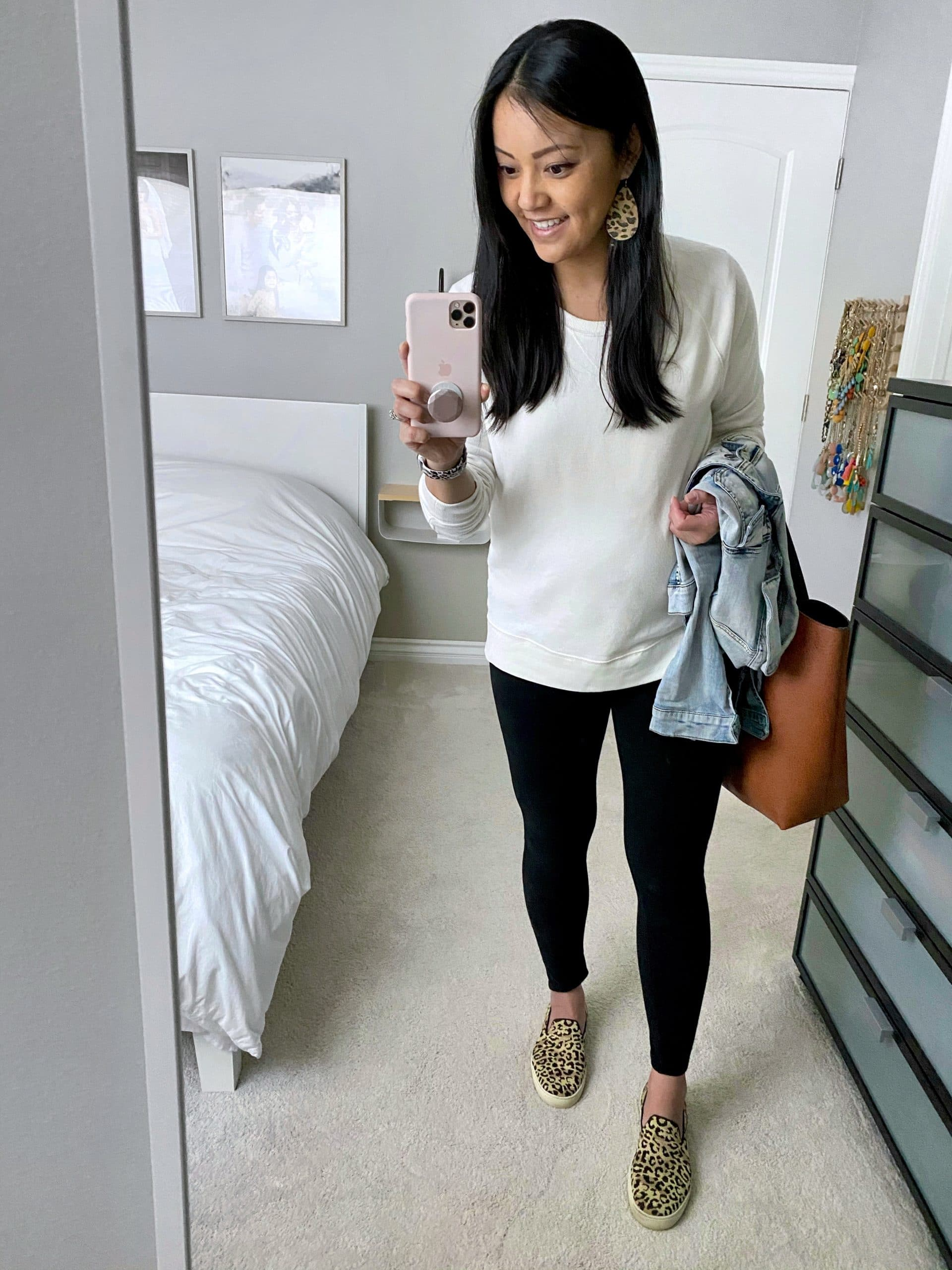Comfy At Home Casual Spring Outfit: white sweatshirt + denim jacket + black leggings + leopard print sneakers + cognac tote + leopard print leather earrings