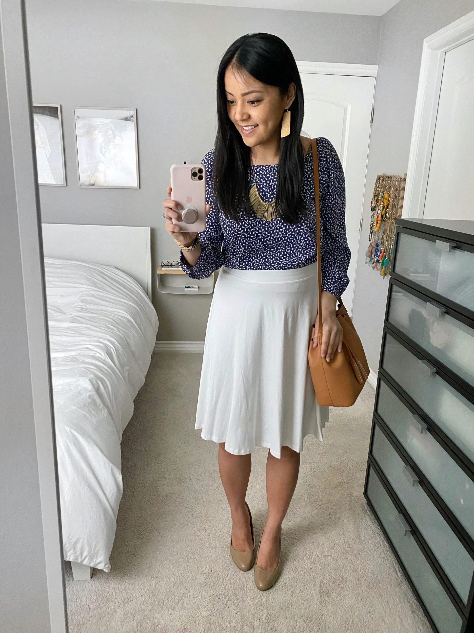 Business Casual Outfit: navy printed blouse + cream knee length skirt + nude patent leather pumps + tan drawstring crossbody bag + gold fringe statement necklace + gold leather earrings