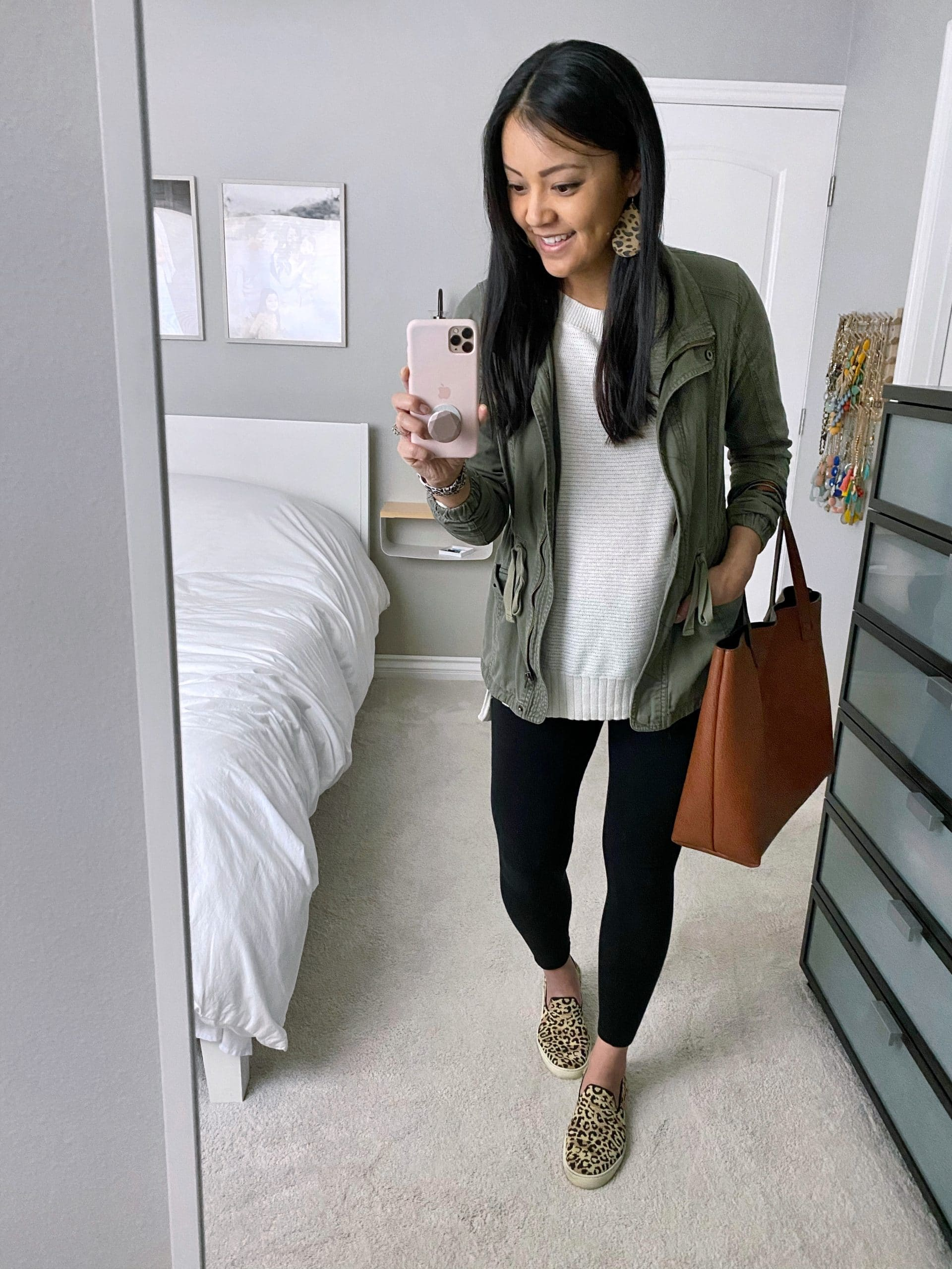 Casual Leggings Outfit To Wear At Home: oatmeal pullover sweater + black leggings + utility jacket + leopard slip-on sneakers + cognac tote + leopard leather earrings