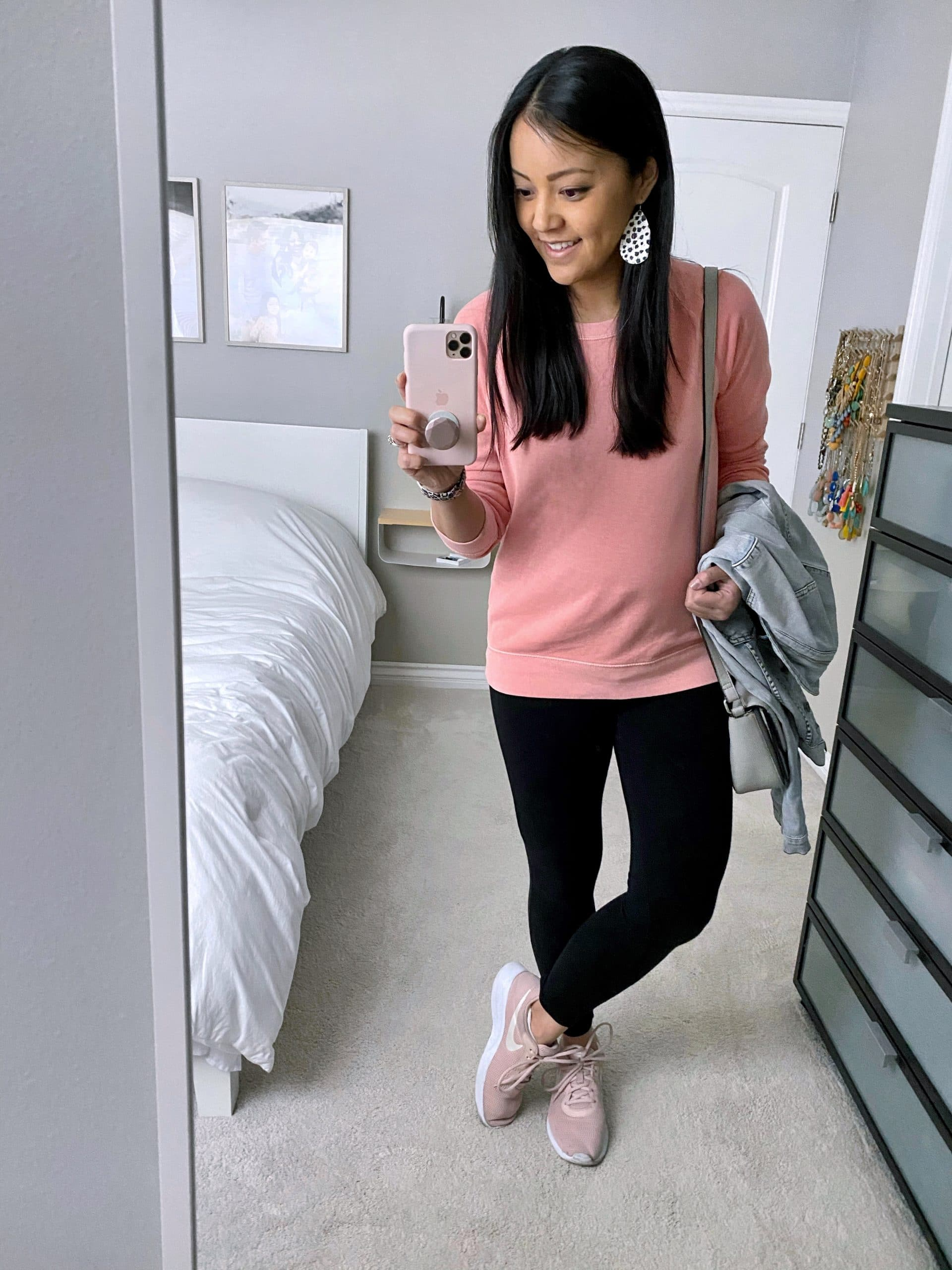 Casual Outfit With Leggings To Wear At Home: pink pullover sweatshirt + black leggings + blush sneakers + denim jacket + grey crossbody bag + leopard leather earrings