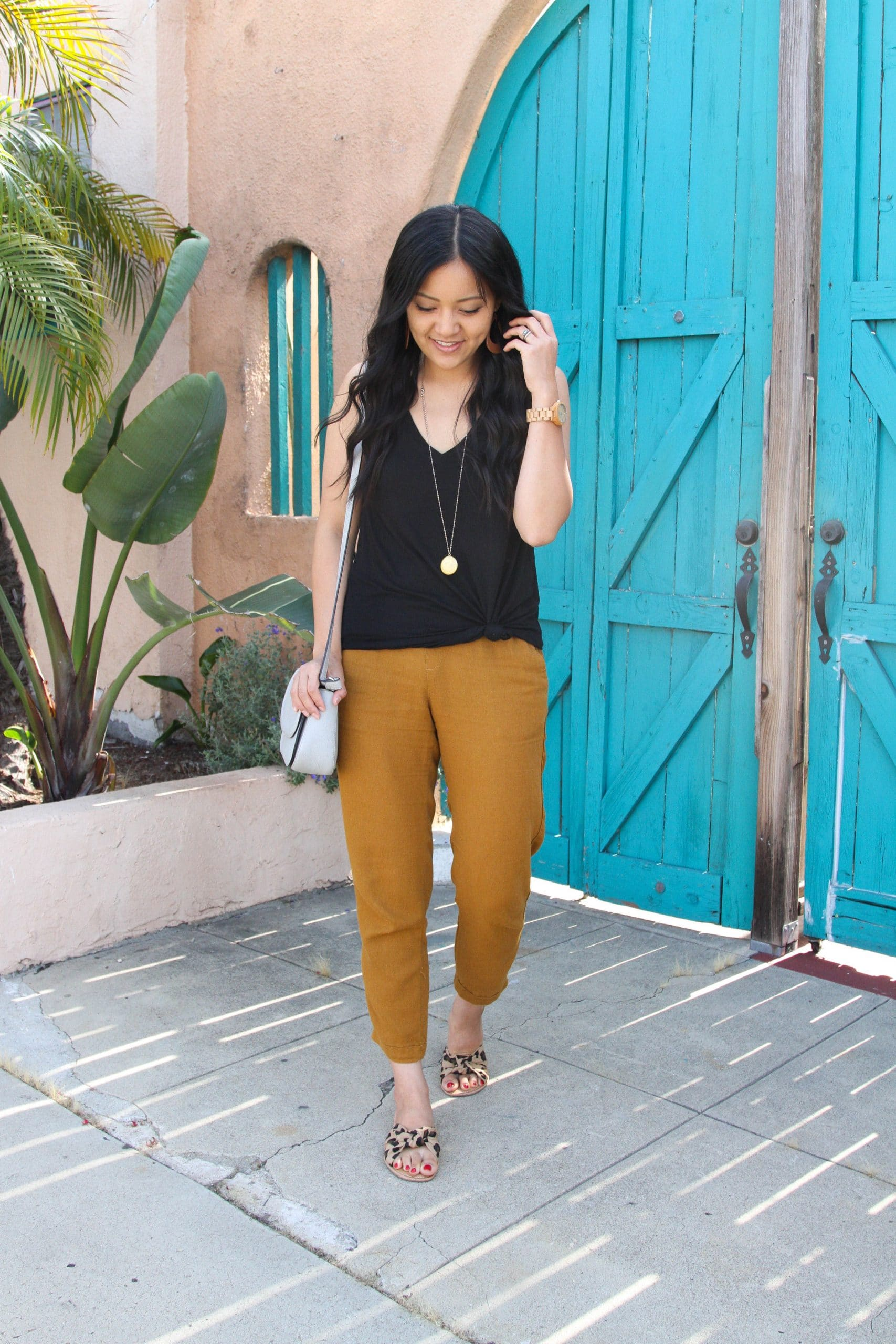 Casual Summer Outfit: black tank top + tan linen pants + leopard slide sandals + grey crossbody bag + long gold disc pendant necklace + tan leather earrings